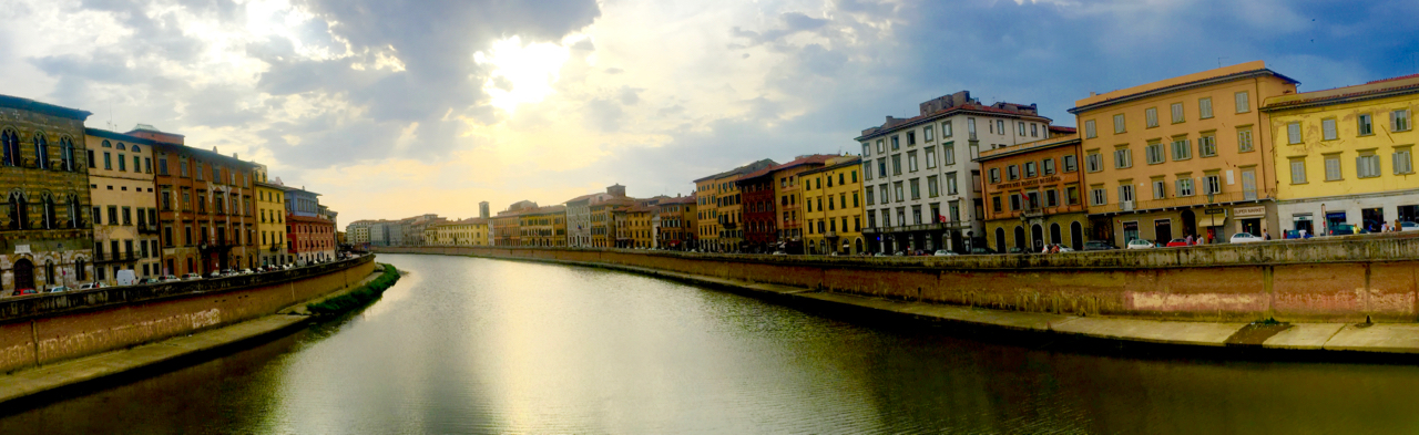 Looking downstream from the  Ponte di Mezzo , located here since 1035 and rebuilt a few times since. The original Roman bridge that preceded it crossed the river on the street next to the eight building on the right. 6:52PM, 23 July, iPhone 6 Plus.