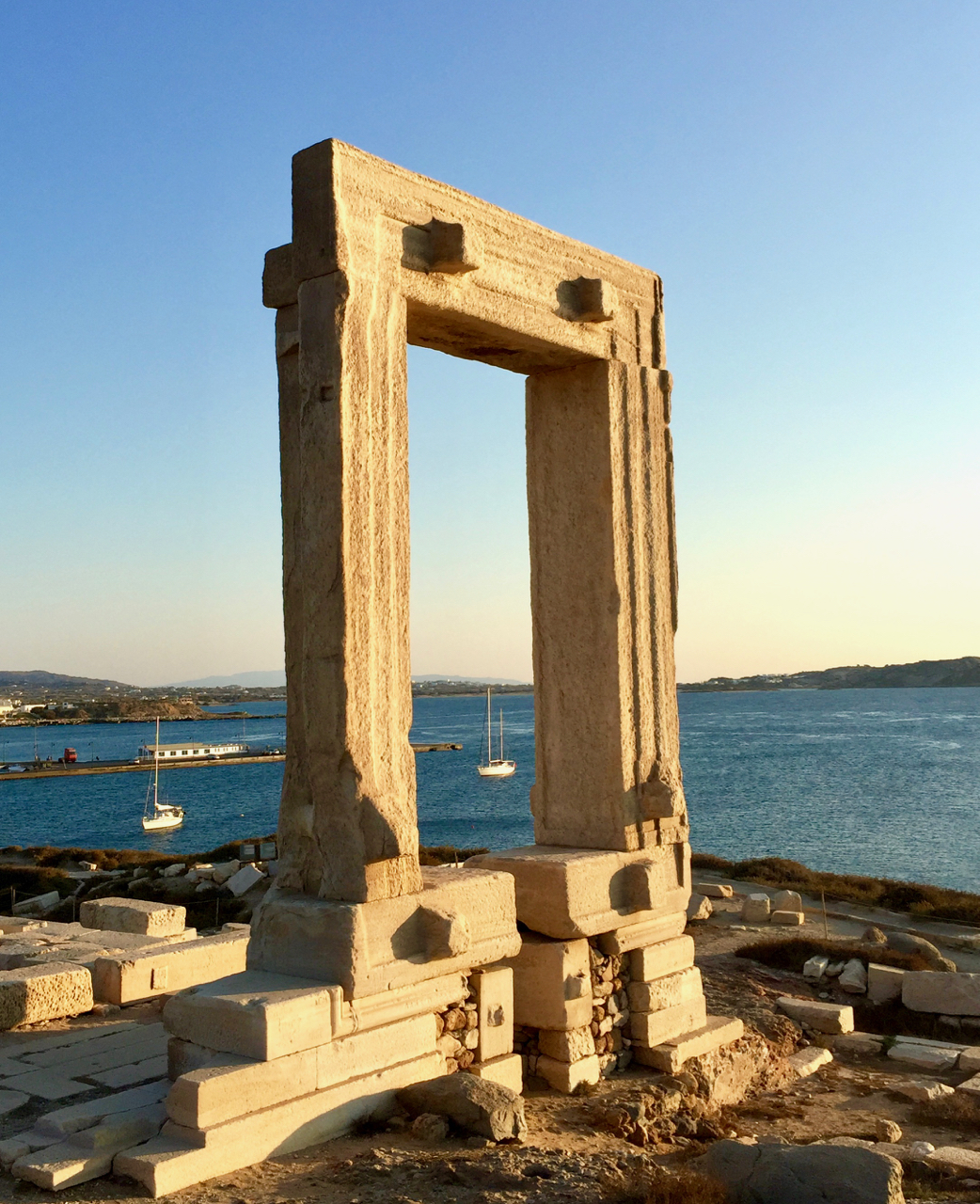 Peregrinus , a white-sailed ship, framed by the 20 foot-tall main door to the 530 B.C. Temple of Apollo. Naxos, 27 September 2017,   iPhone 6 Plus.