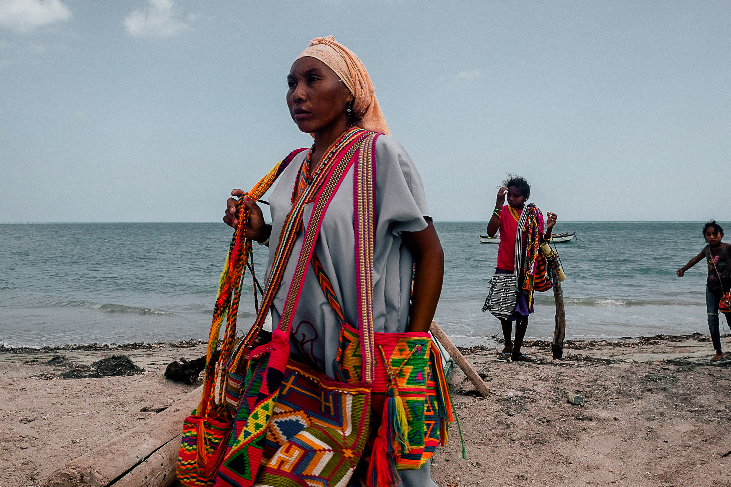 Merchants selling handmade patterned bags on the coast in Riohacha.