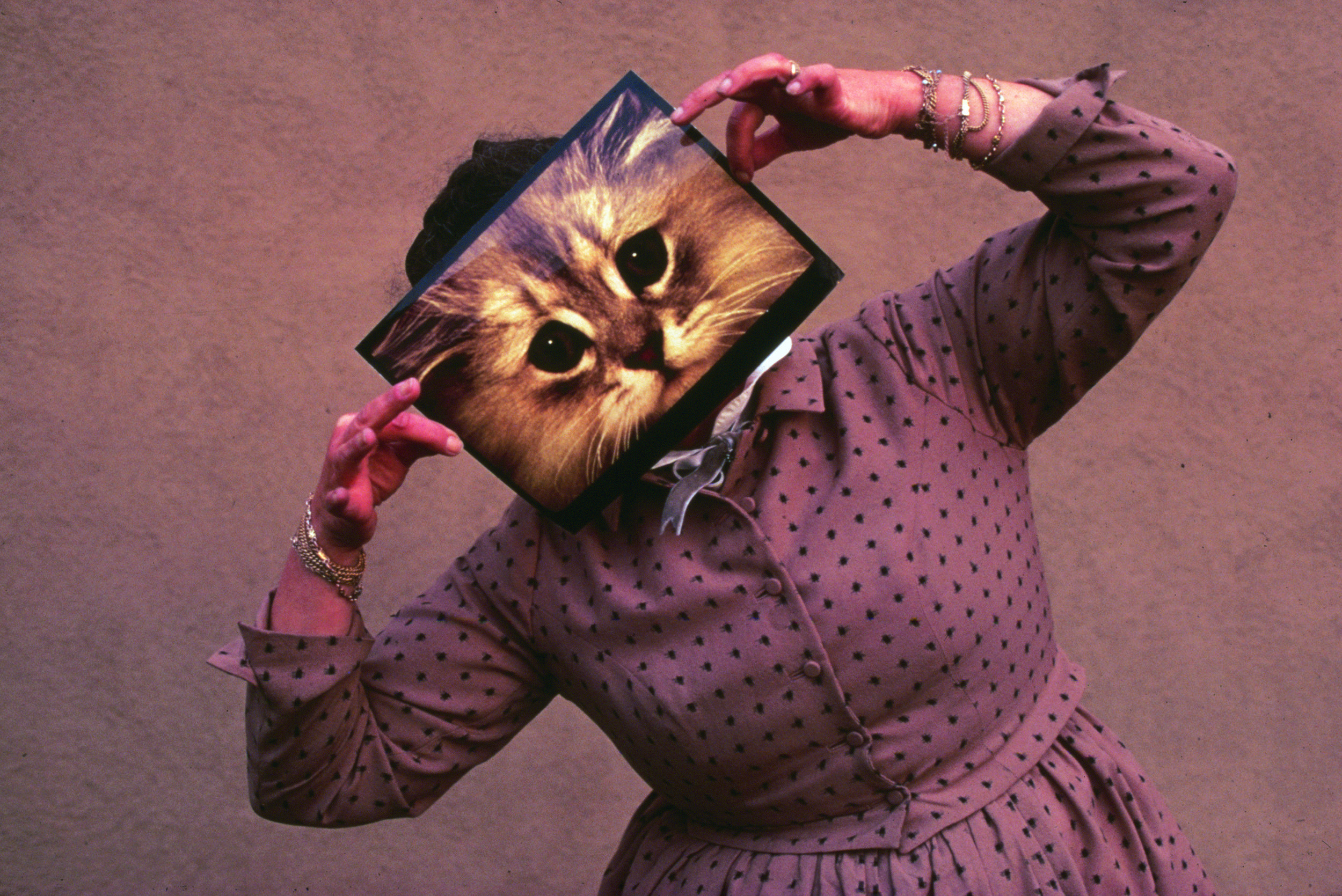 06. An Eames Celebration. Ray Eames posing with a cat photograph, December 1970. ∏ Eames Office LLC.jpg