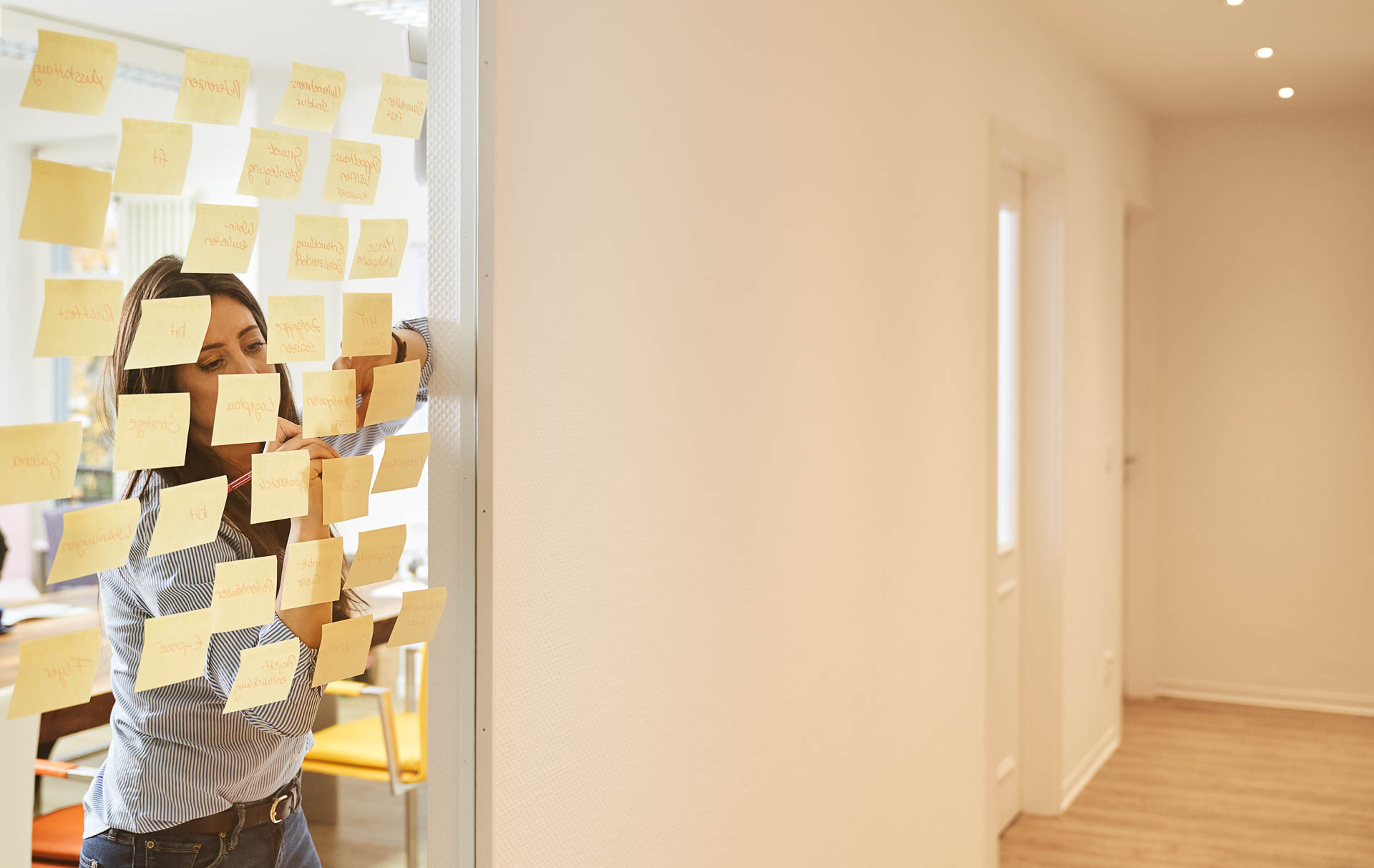 Corporateshooting für die neue Webseite und zur Gewinnung von neuen Mitarbeitern. Fotografiert in einer Villa in Berlin Zehlendorf. Mitarbeiterin lehnt am Fenster und schreibt Notizen auf Post Its.
