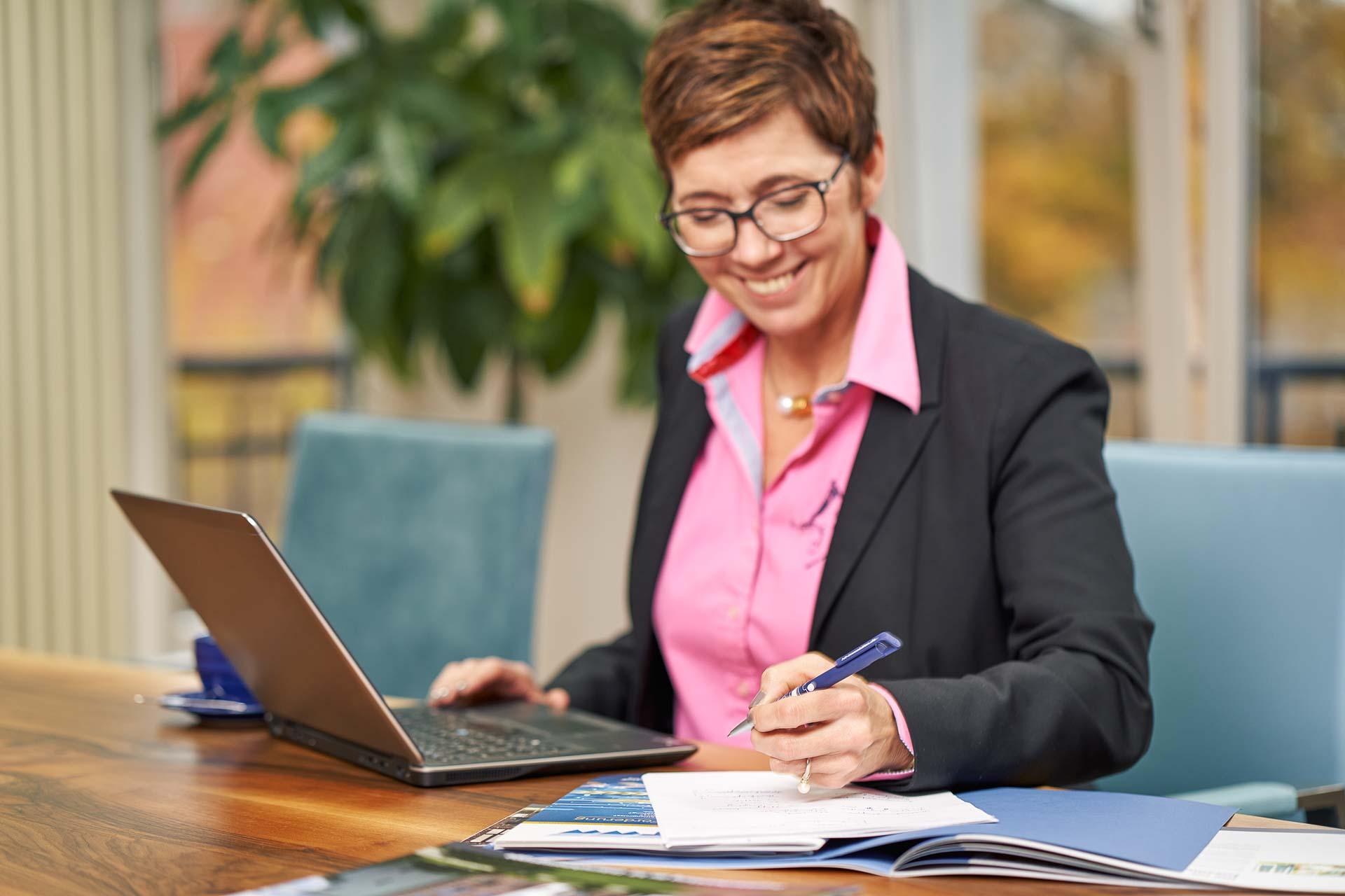 Corporateshooting für die neue Webseite und zur Gewinnung von neuen Mitarbeitern. Fotografiert in einer Villa in Berlin Zehlendorf. Mitarbeiterin notiert sich etwas auf einen Block und lächelt dabei.