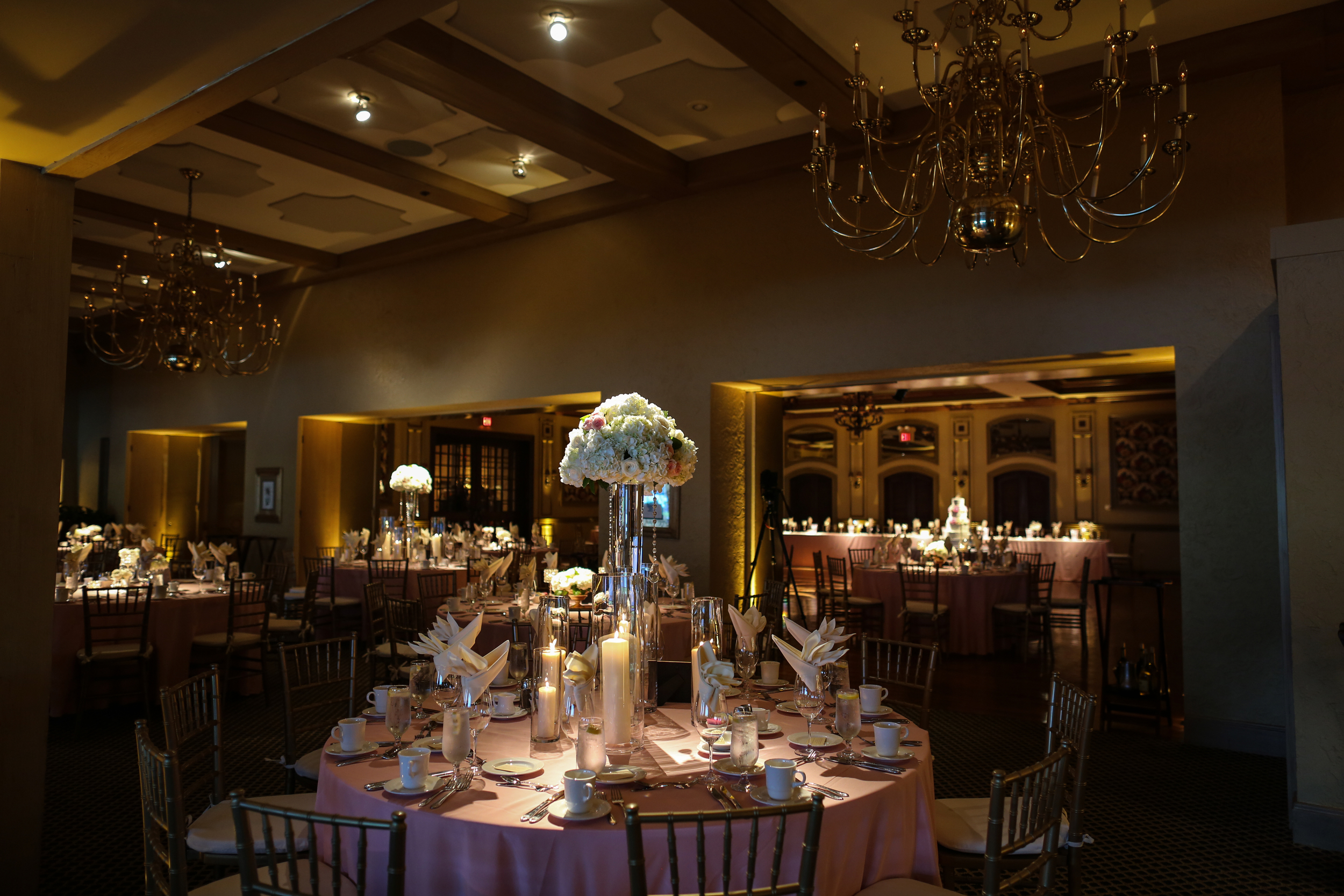 Spread throughout the reception were tall Pilsner vases filled with ivory Hydrangea, White Dove Roses, Lemon Leaf, and Starblush Spray Roses. Hanging crystals brought Katie's vision to life.