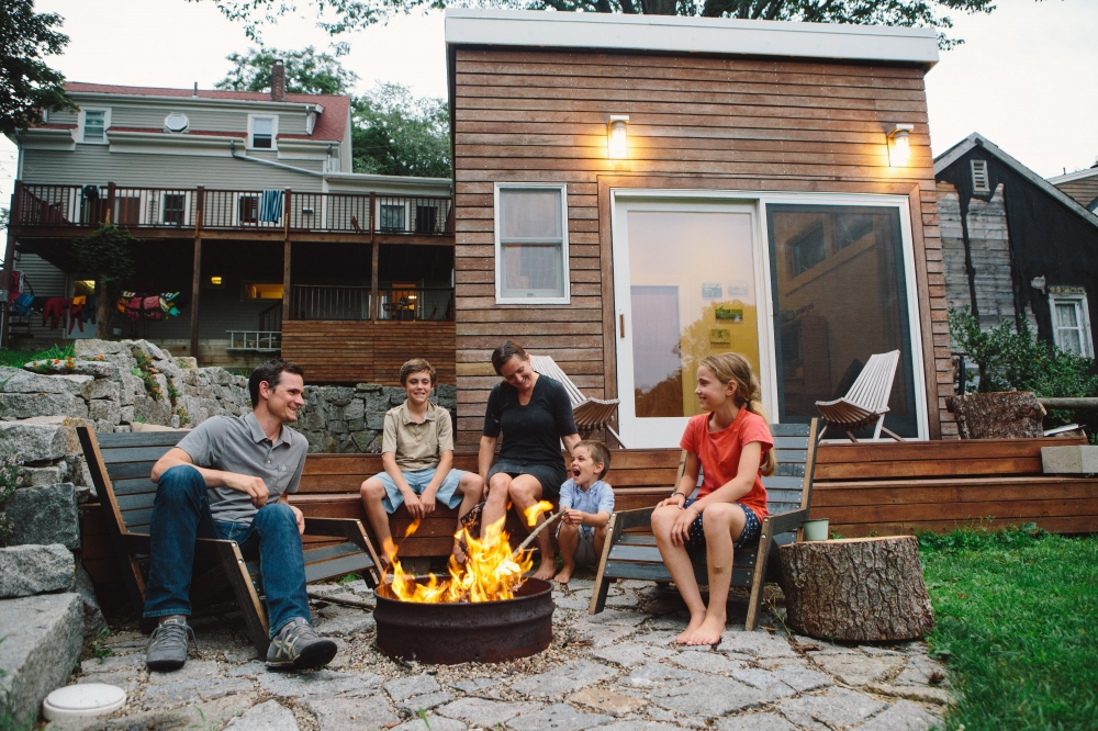 The family enjoys the fire pit, made from a recycled oil drum. (Photograph by Mark Spooner)