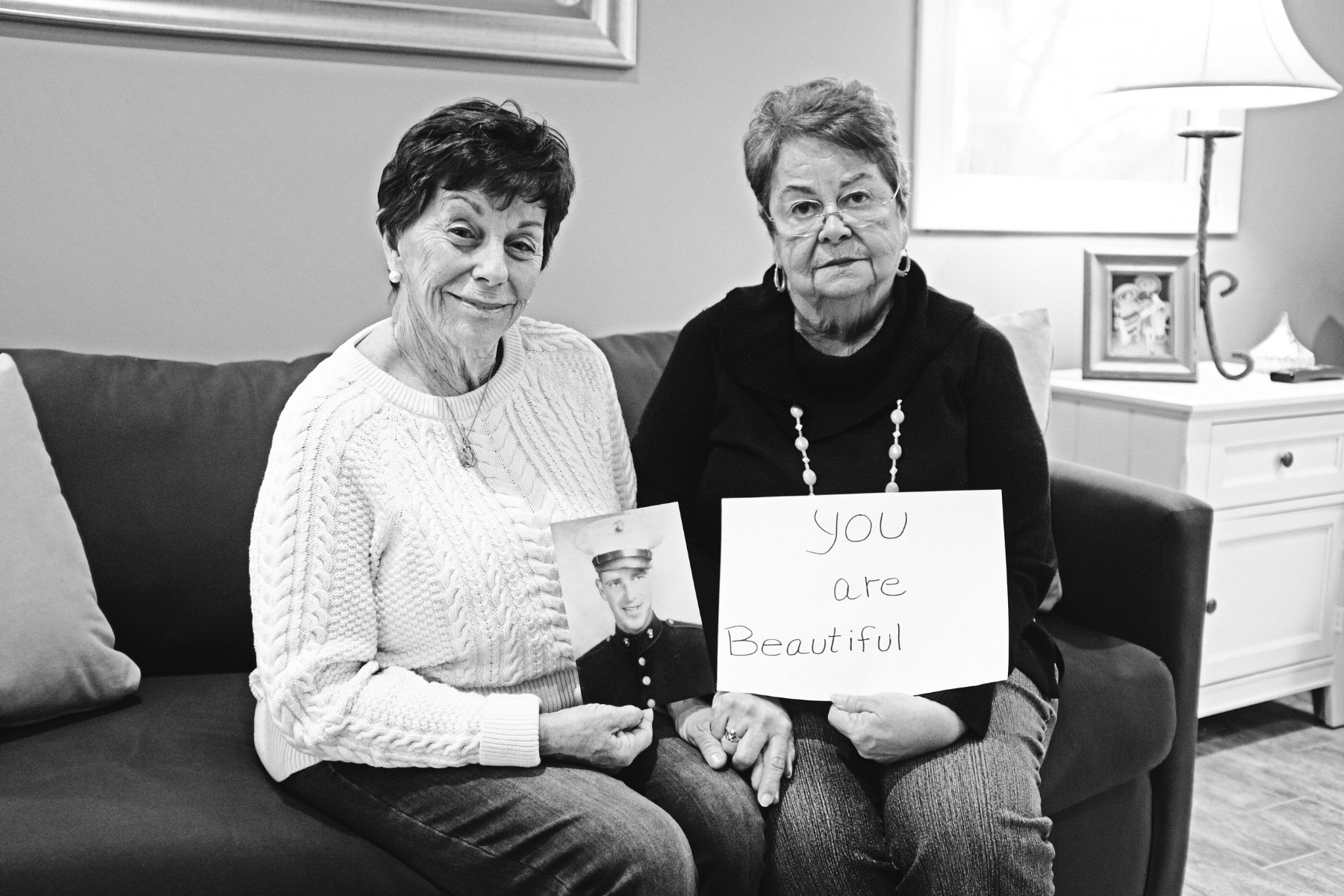"Judi Bove and Eileen Pereira hold a ""you are beautiful"" message for their father, Ralph Greely. He was killed in action in the Marine Corps during World War II while the sisters were small children. They got to know him through stories and letters. (Photograph by Thi Linh Wernau)"