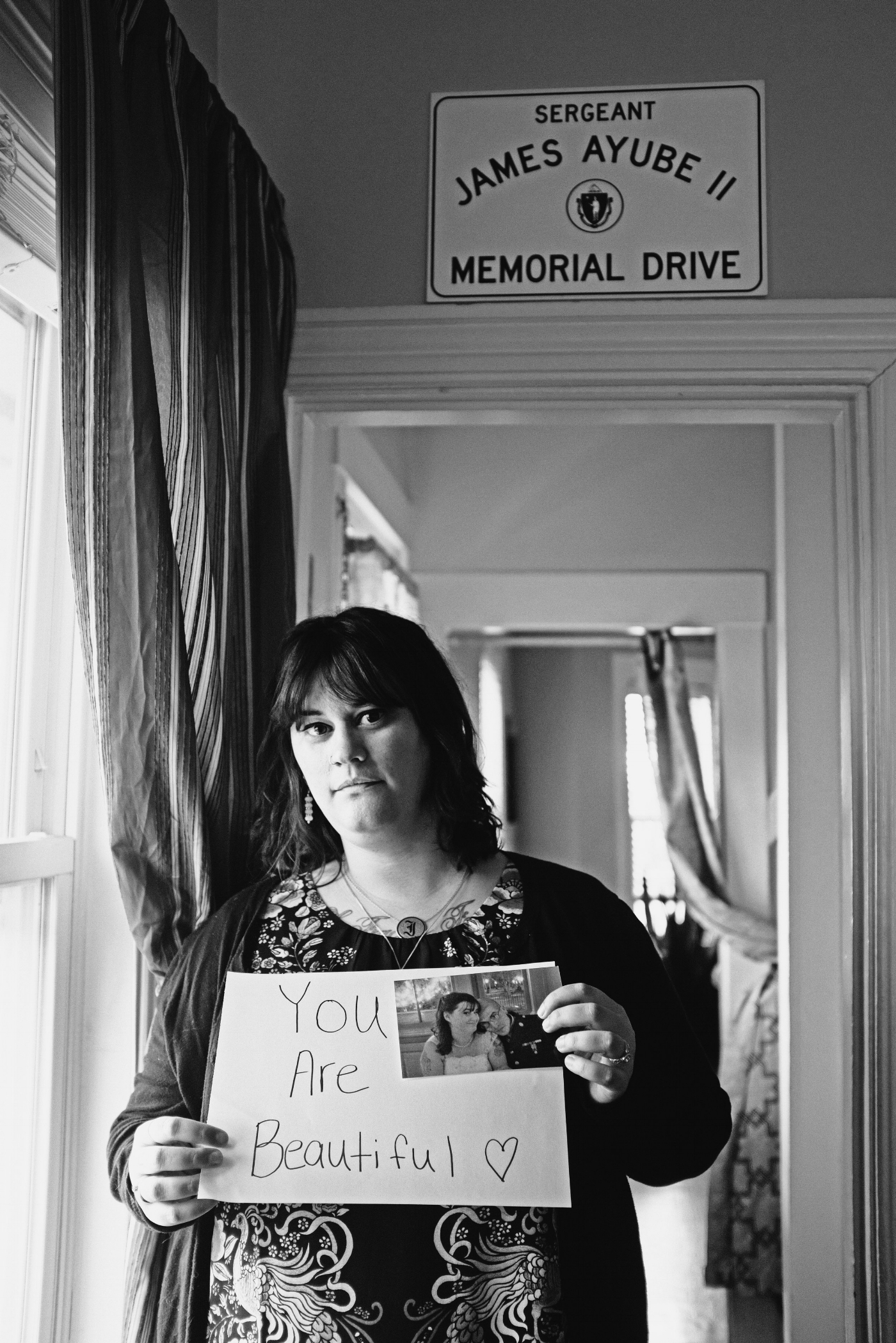 "Lauren Ayube holds a ""you are beautiful"" message for her husband, James, together with a photo from their wedding day. Lauren lives in Salem where there is a bypass road named in honor of James. Following her husband's death, Lauren dedicated her work to outreach for veterans and is pursuing a Master of Social Work. (Photograph by Thi Linh Wernau)"