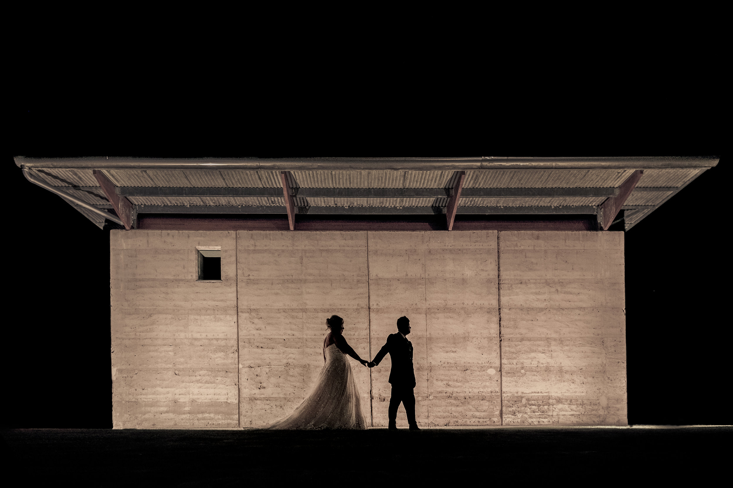 Bride and Groom walking together at night
