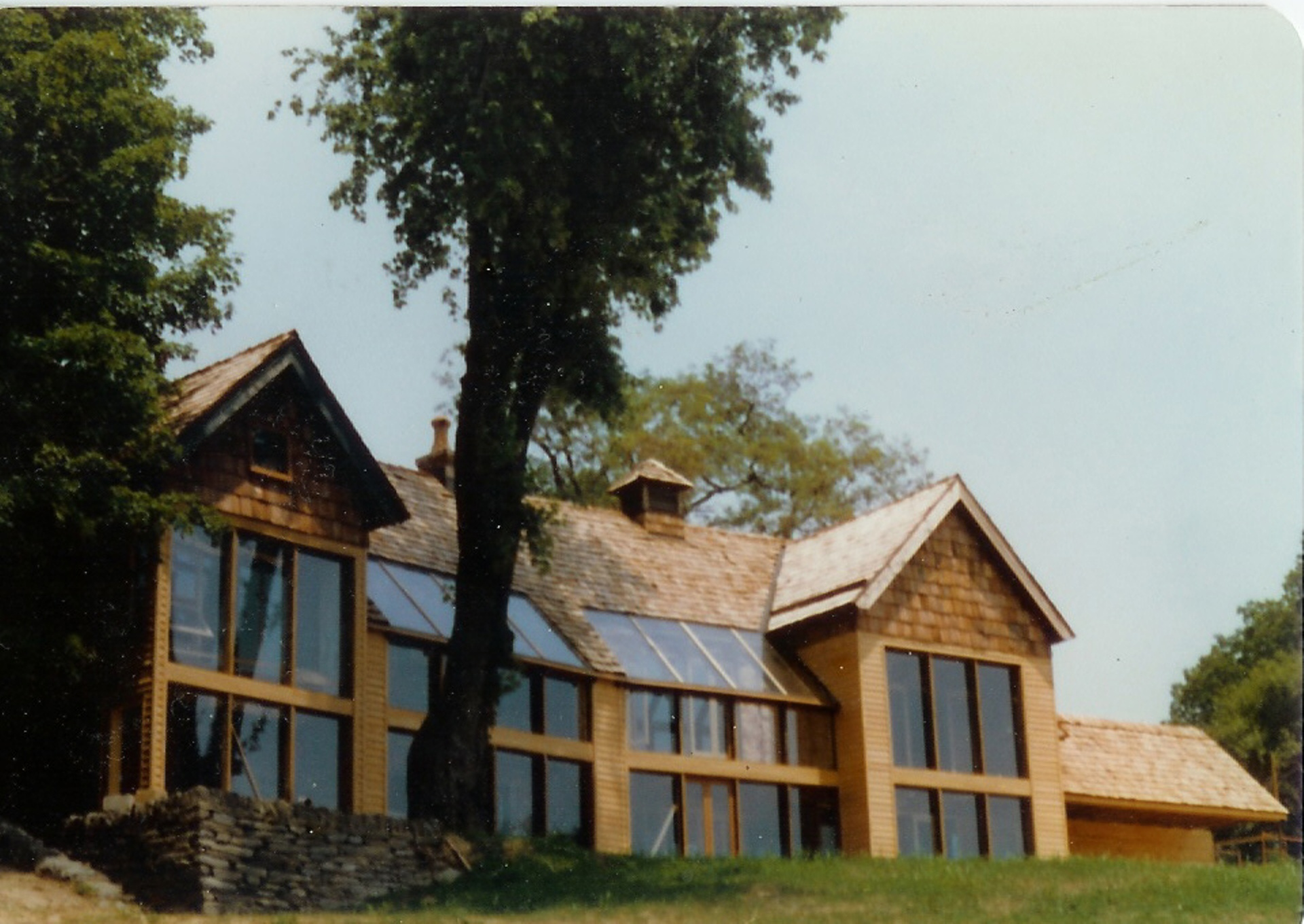 Built in 1979 this 3,600 square foot house had only a wood stove for back up. Behind the west half of the south glass wall is an old stone farm house. All this stone provided a large thermal flywheel that kept the house warm in winter and cool in summer.