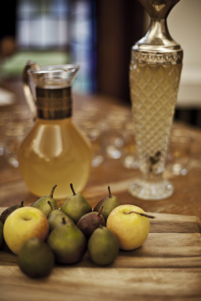 Pears and apples on a wooden cutting board with drink decanters in the background at an Edible History 15th century italian feast.jpg