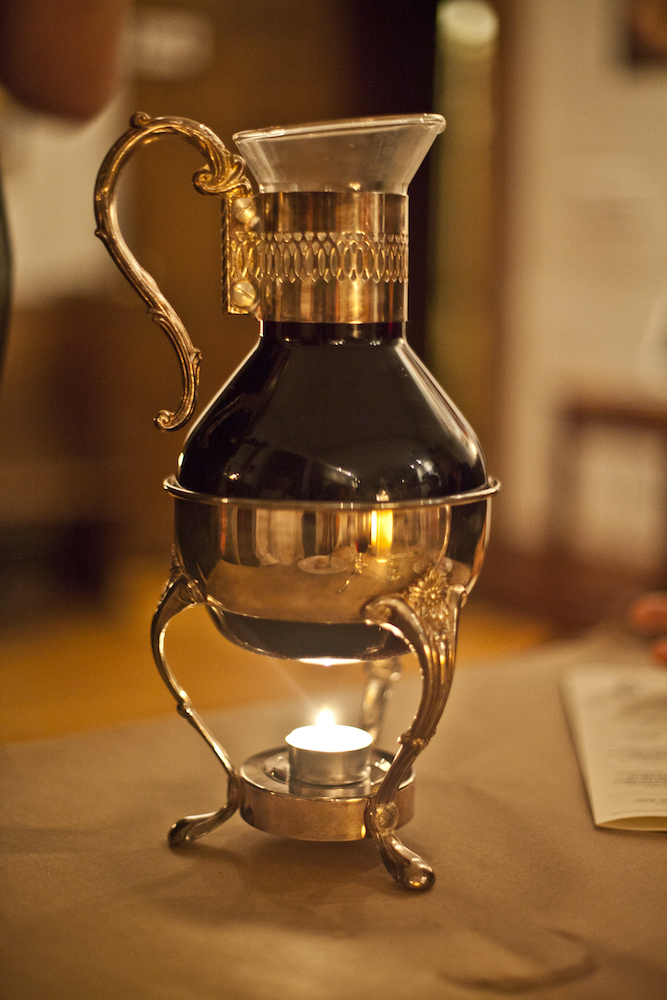 Liquid in metal and glass container heated by candle at Edible History's 15th century italian feast.jpg