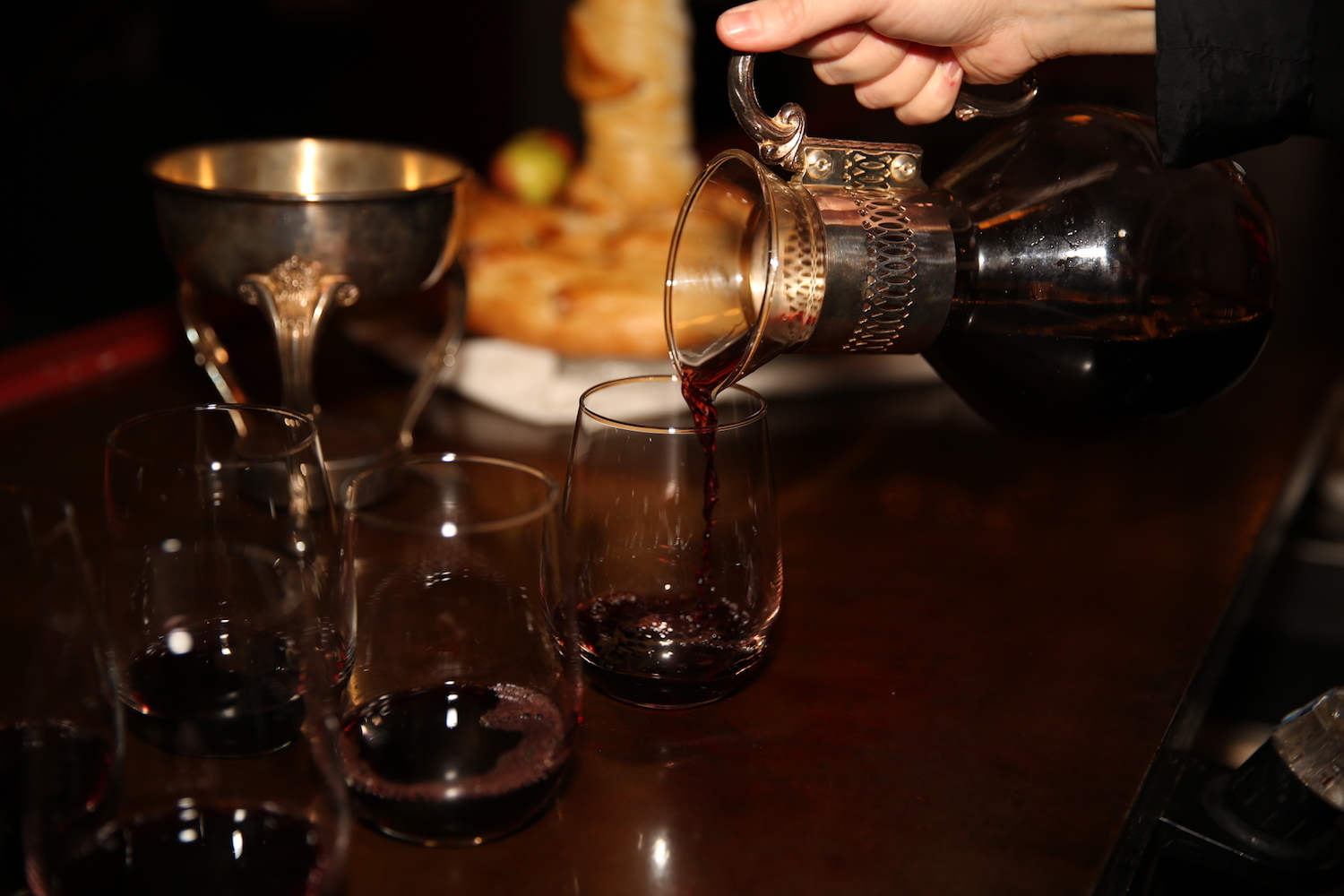 Pouring red wine from a vintage decanter into stemless wine glasses.JPG