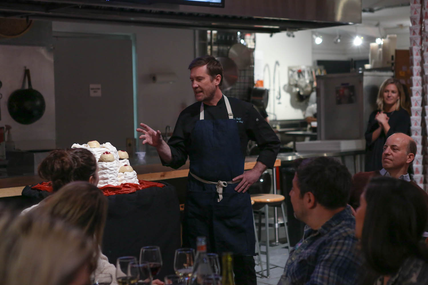 A chef standing in front of a crowd at an Edible History dinner.jpg