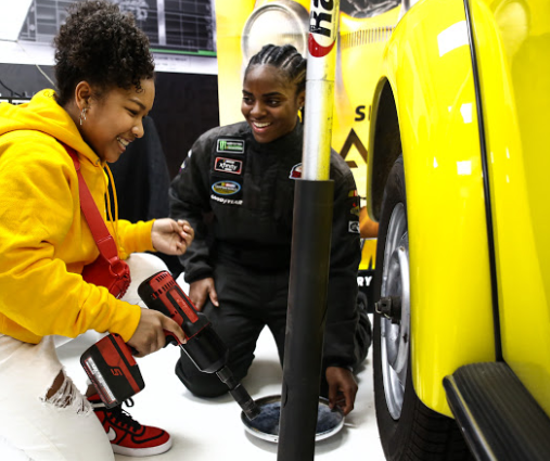 (L-R) Laya DeLeon Hayes learns to change tire from Brehanna Daniels at the Glammed-Out Auto Clinic at West Coast Customs on behalf of BUMBLEBEE, in theatres December 21 (Photo Credit: Steven Baffo)