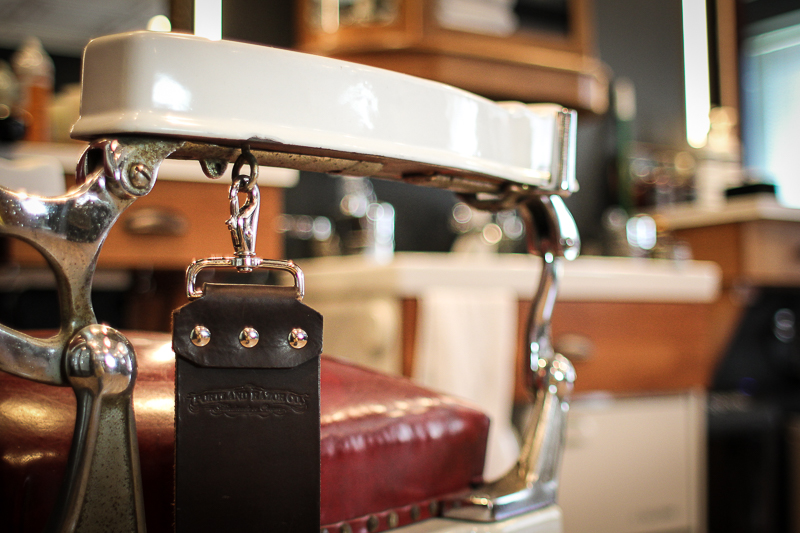 A Portland Razor Co. Deluxe strop hangs from a vintage barber chair strop hook.