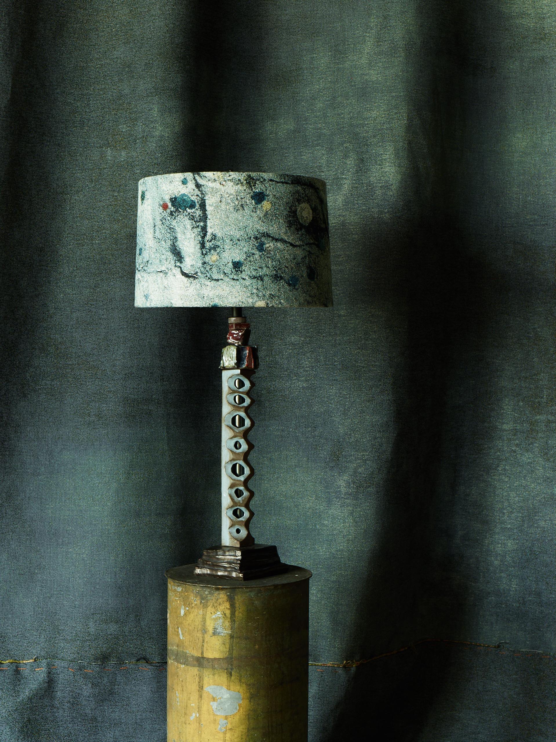 """Copy of """"Totem"""" lamp in front of """"Watercolor, Khaki"""" jacquard."""