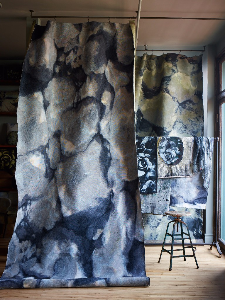 """Fabric drops of our  """"Rock Pool"""" and """"Ripple"""" jacquards  frame the studio fabric rack that is filled with fabric samples, including pieces of our """"Melting Rose"""" in Sky Blue."""