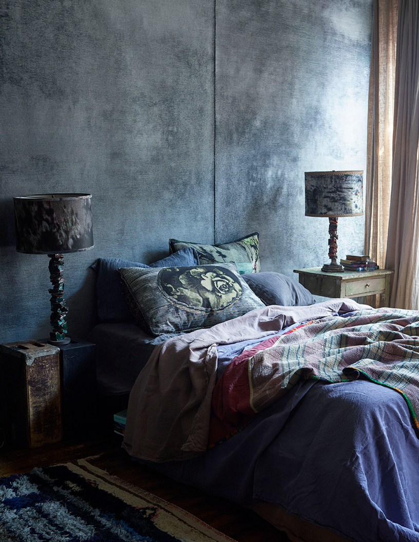 """Martyn's bedroom features walls upholstered in our """"Watercolor"""" jacquard (launching March 2018), a  selection of our King Euro tapestry pillows  and a pair of """"Quarry"""" lamps by MTS and Dove Drury Hornbuckle."""