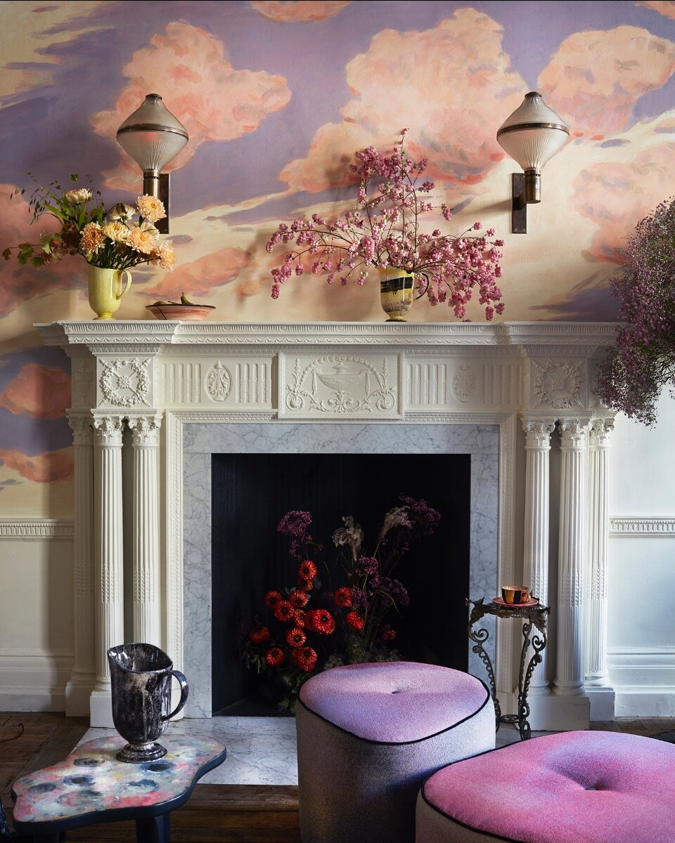 "Cloud mural by Charlotte Lawton. On the mantle are hand painted jugs for 1882Ltd with flowers from Wild at Heart. MTS ottomans in Dream ""Pinkish""."