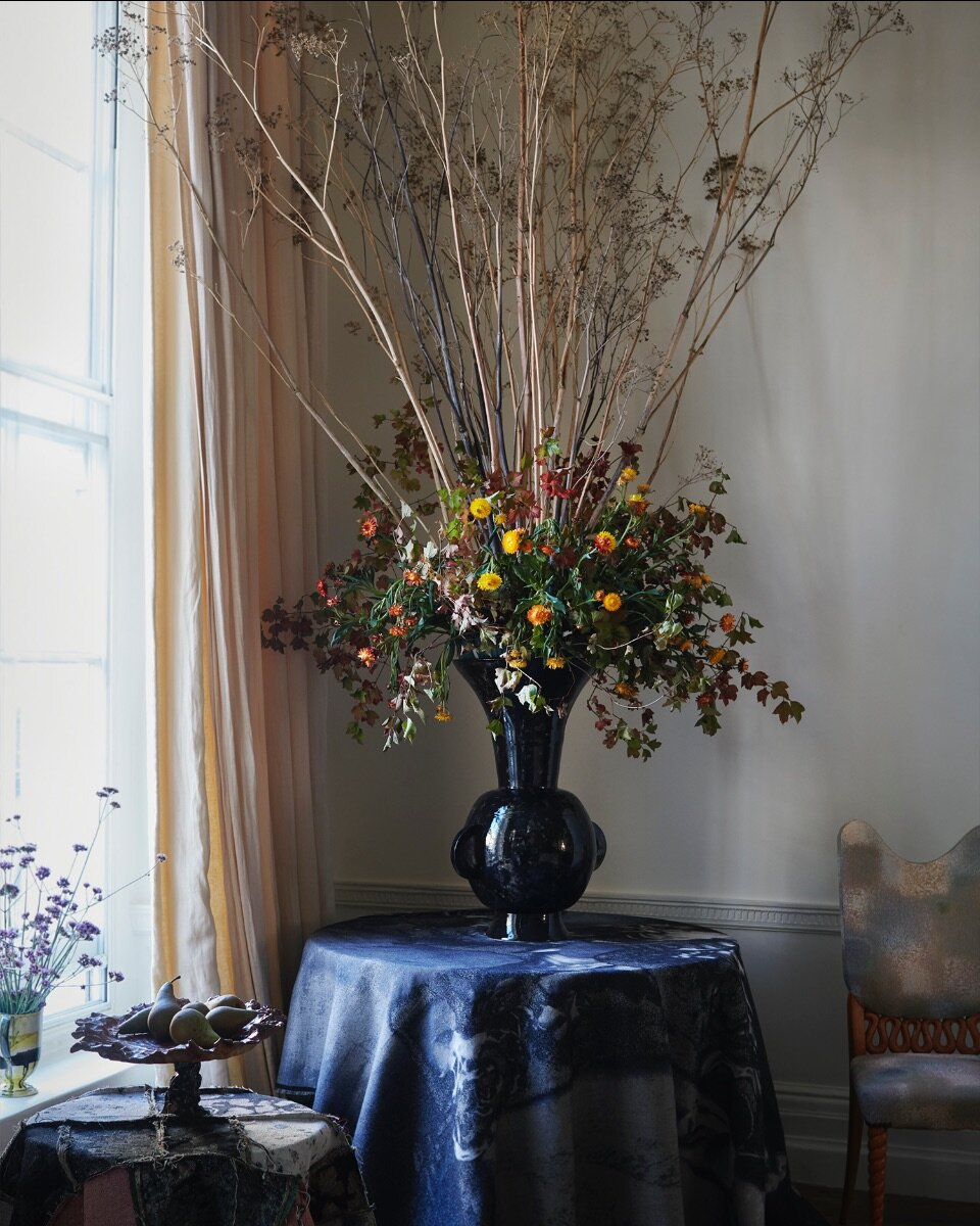 The black Penny vase from 1882Ltd in a fountain of forestry from Nikki Tibbles Wild at Heart. Jacquard textiles from MTS.