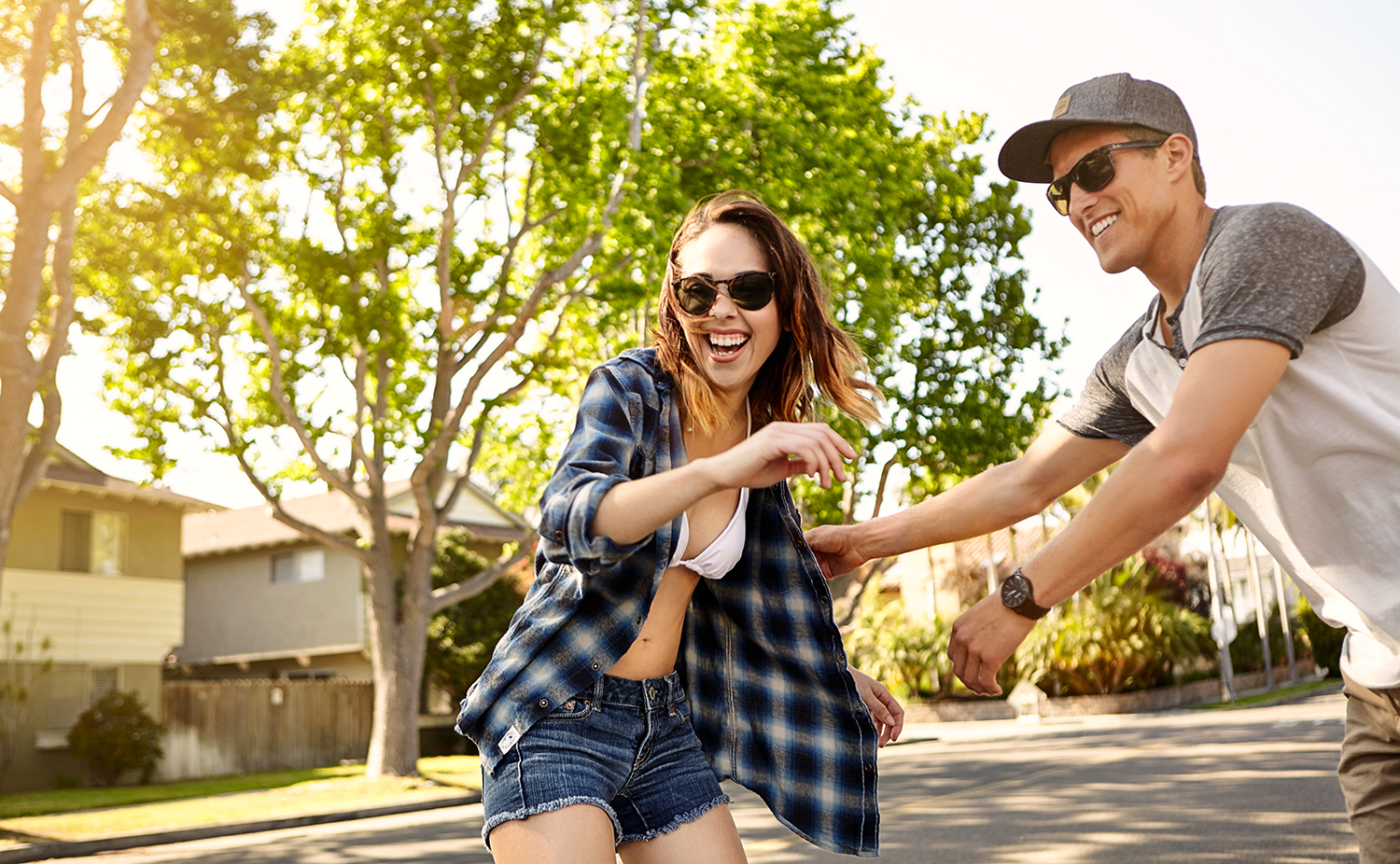 lifestyle guy and girl flurting playing on skateboard in street.jpg