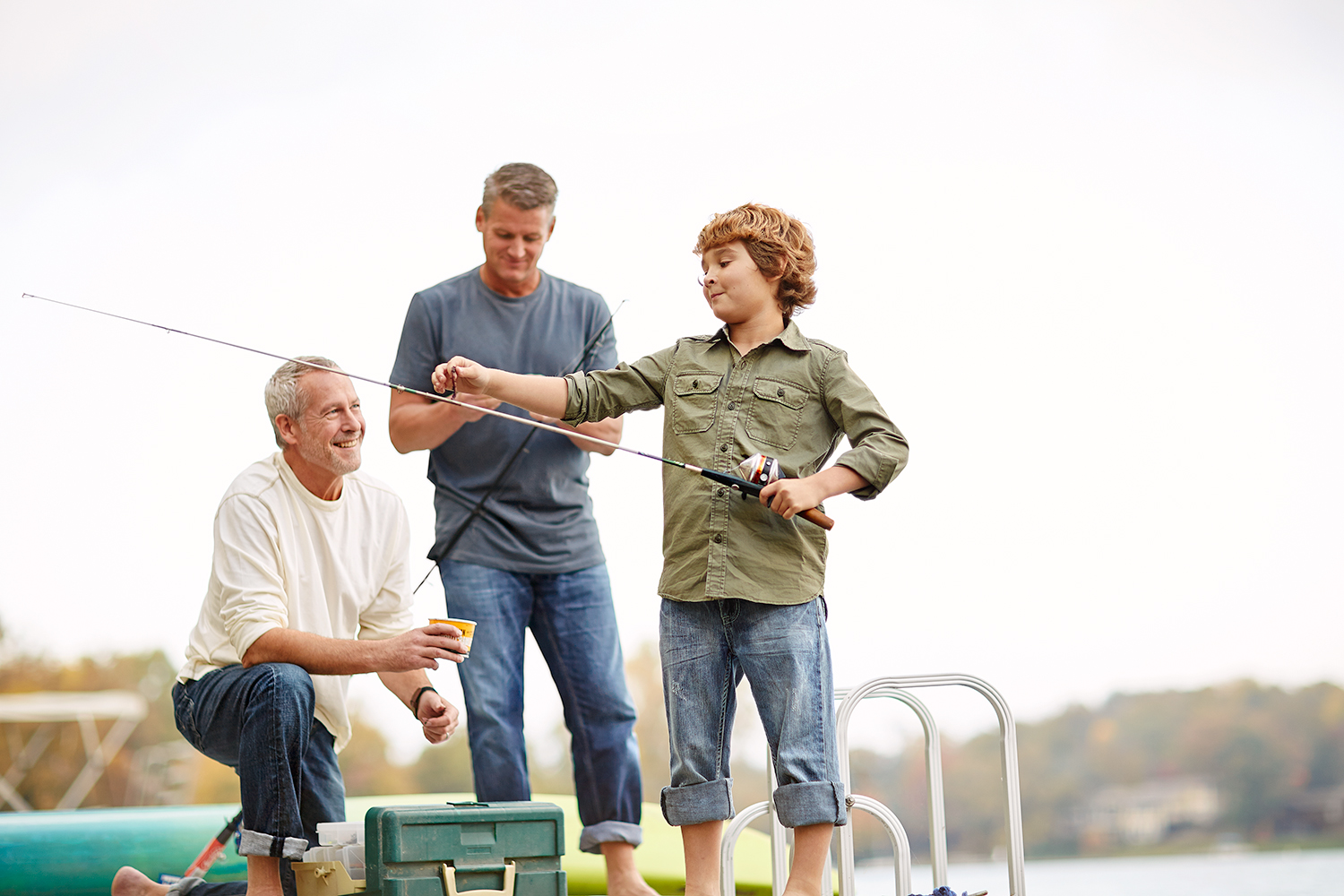 boy fishing with father and grandfather on lake dock with poles.jpg