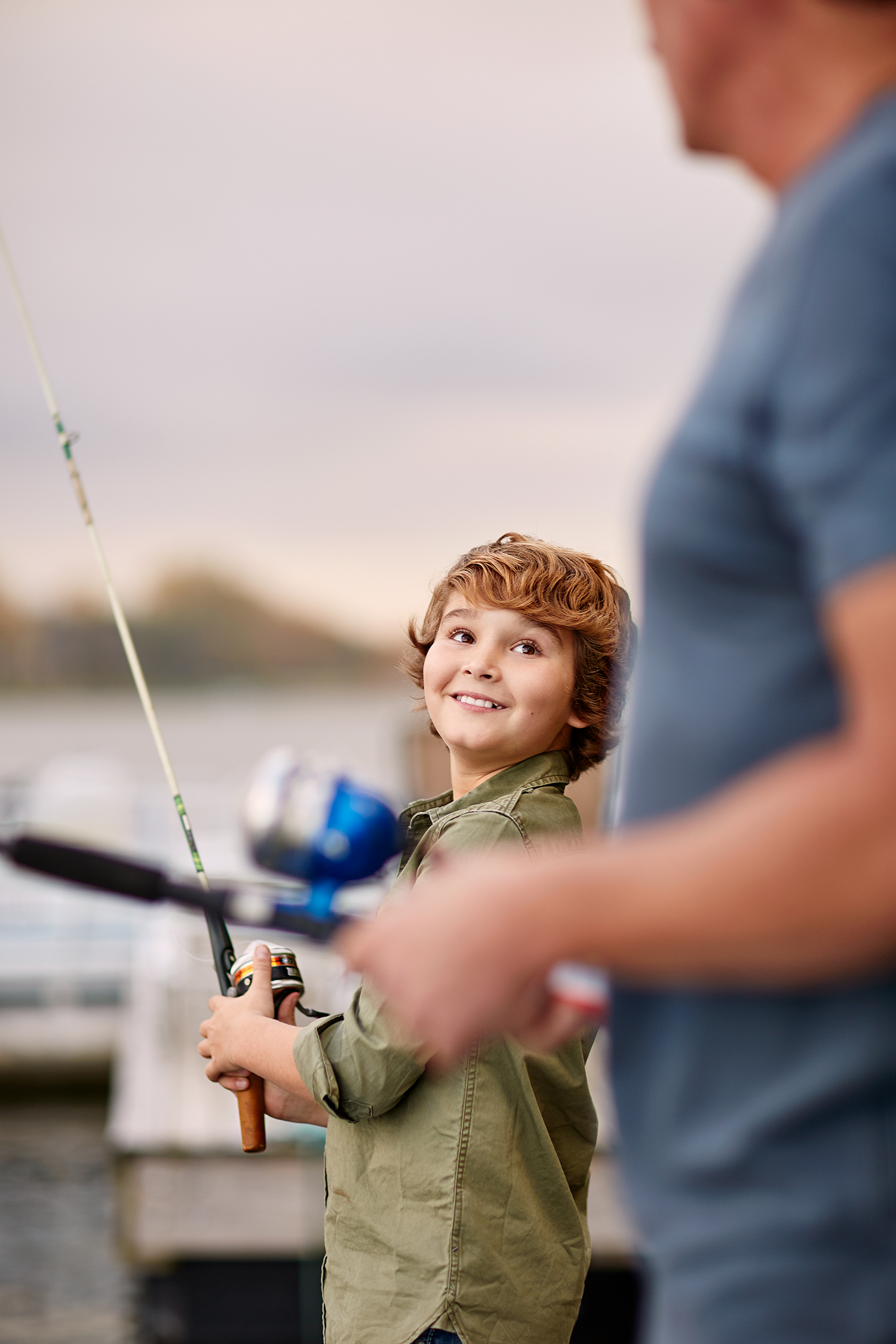 boy smiling at dad with fishing pole on lake dock.jpg