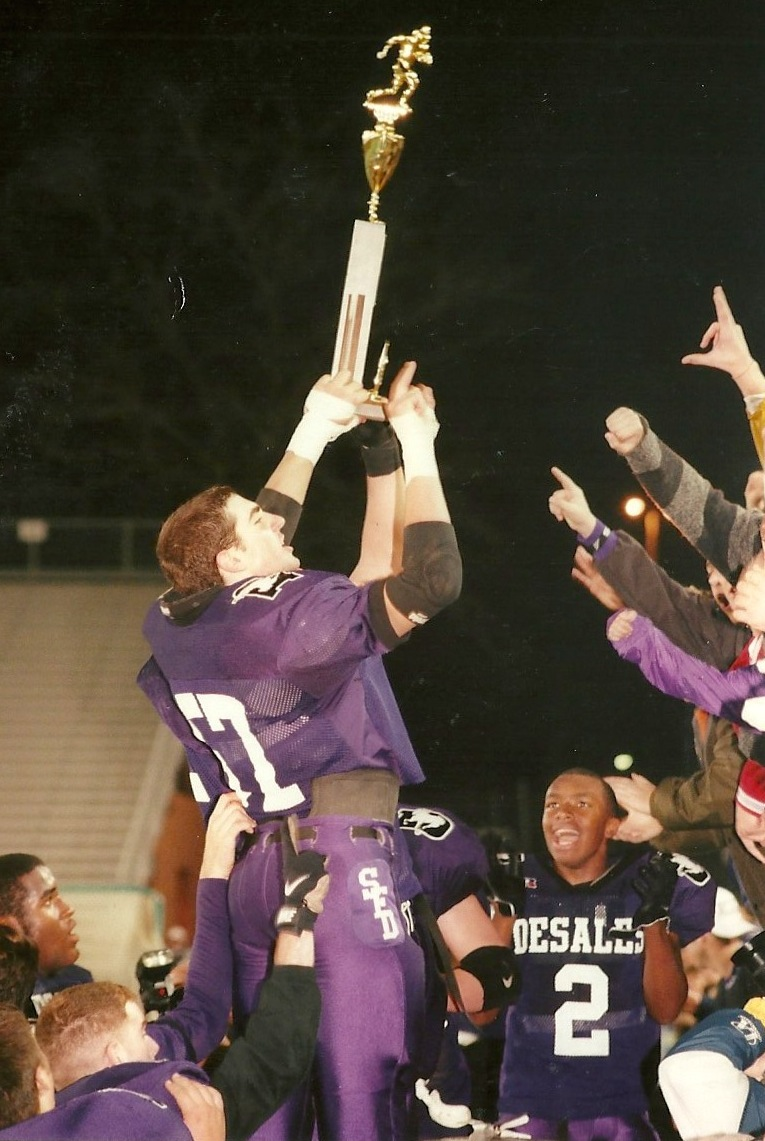 Joe Dura (57) shows off the trophy to the Stallion fans