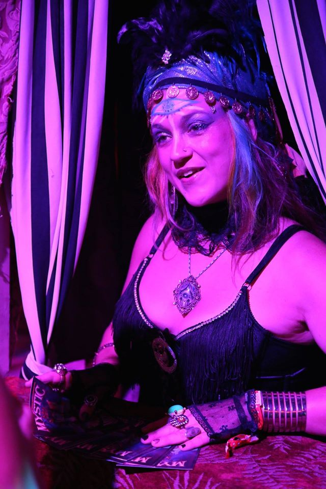 Lady Fortuna gives Mystic Midway Storycard readings to guests from her oracle booth