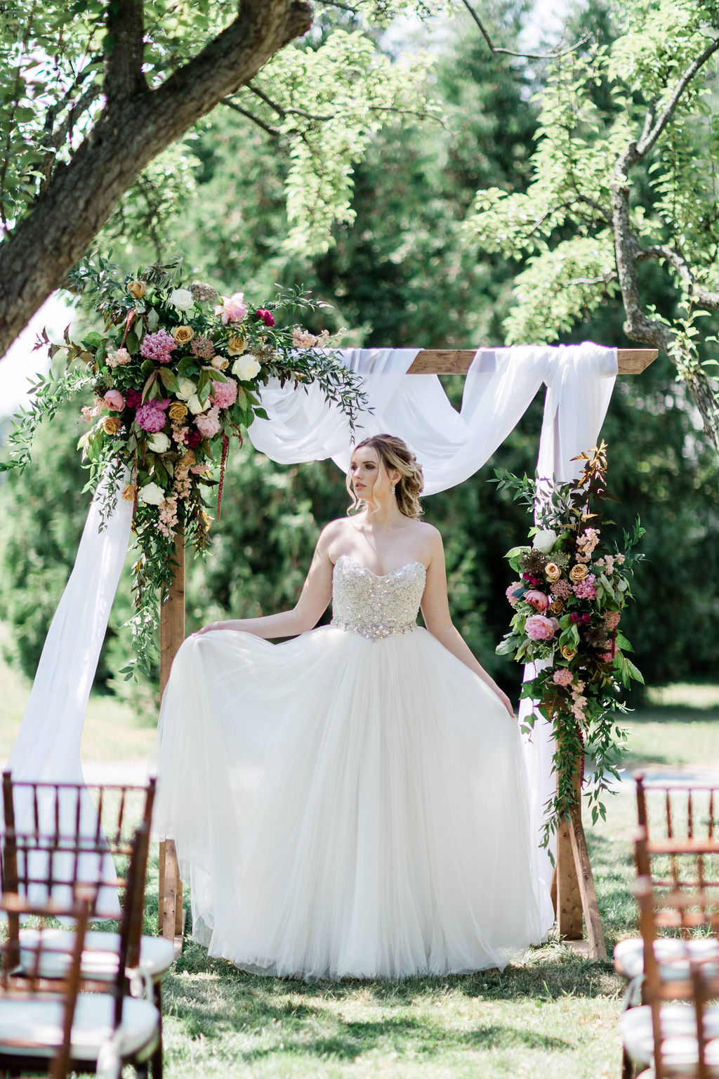 A bride standing under a floral archway at Kurtz Orchards in Niagara-on-the-Lake with a flowing white dress