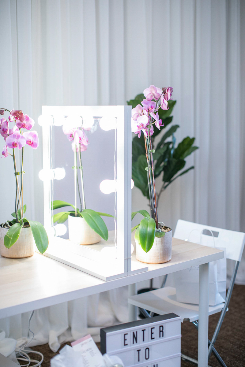 bridal hair and makeup booth with orchids and lights