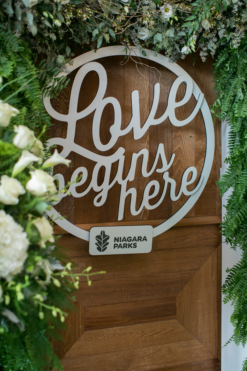 closeup image of love begins here wood hanging sign