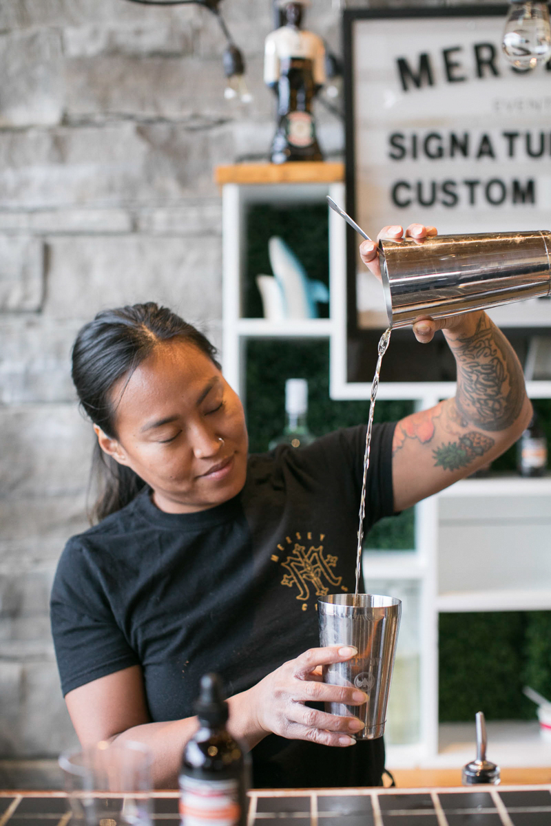 employee mixing and pouring custom cocktails
