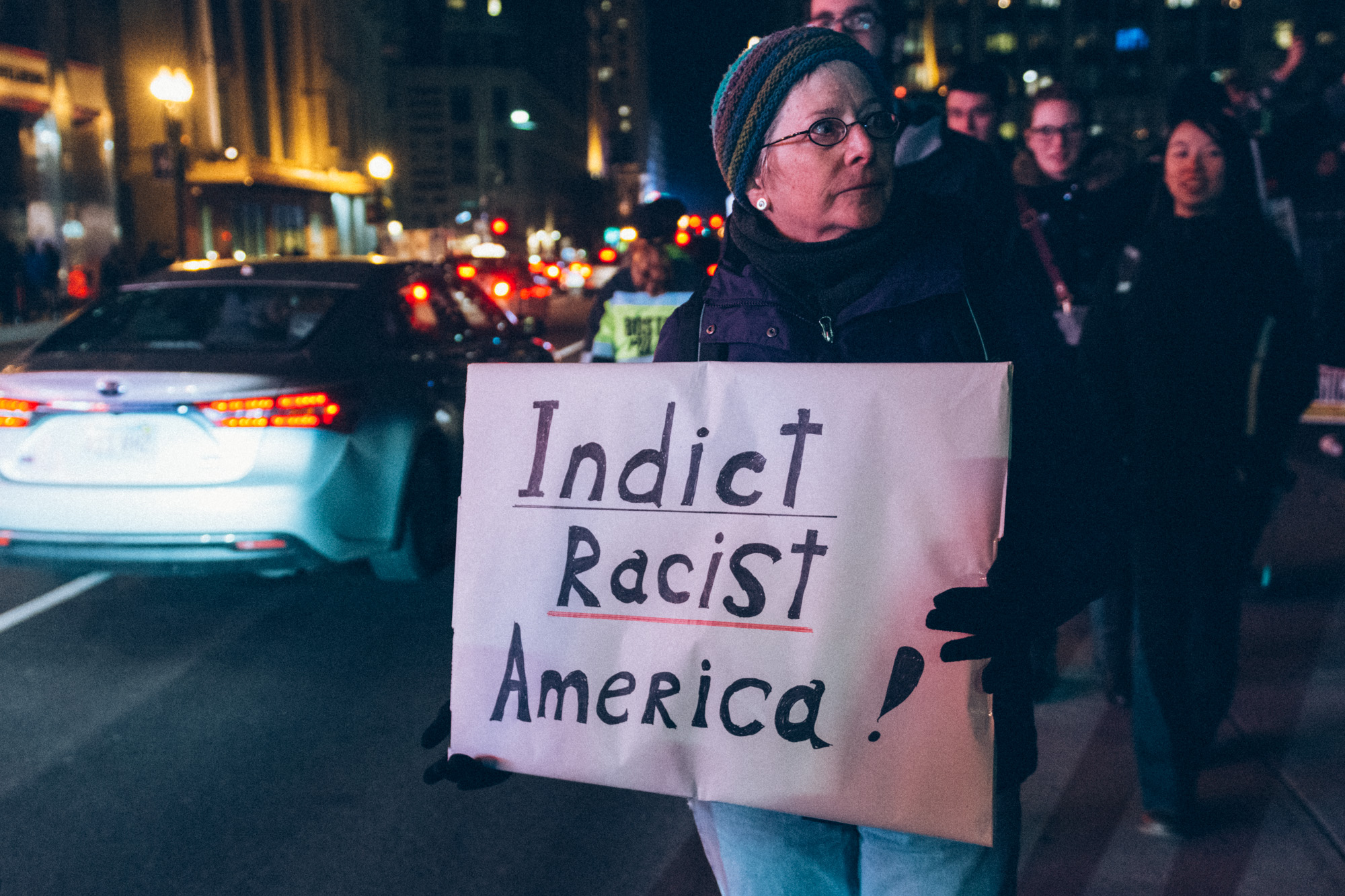 A woman standing with a sign on Tremont Street, just outside the Commons.