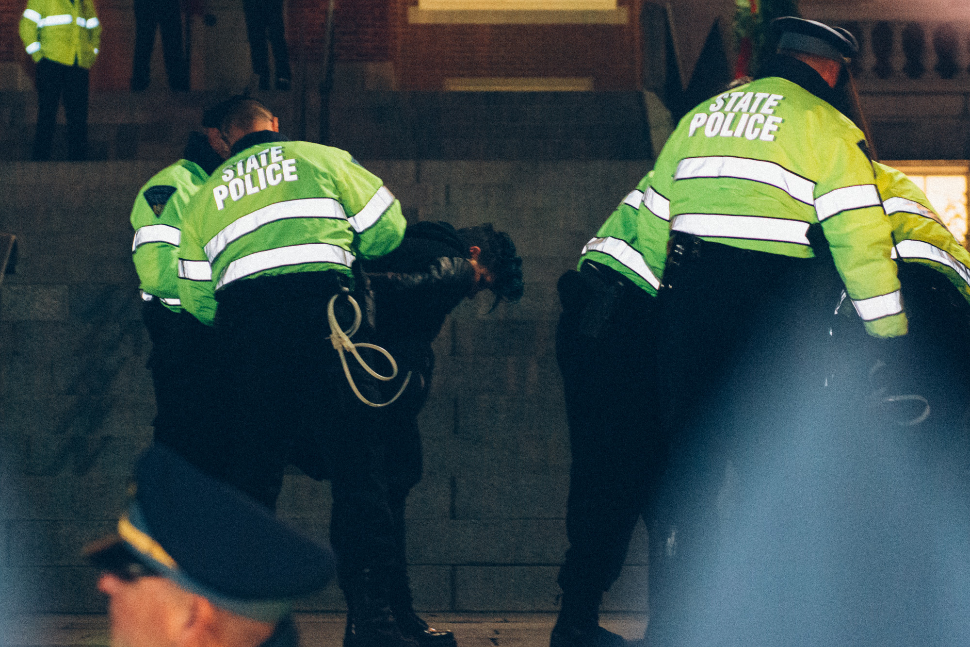 One of the three arrested protesters at the state house being arrested by the state police.