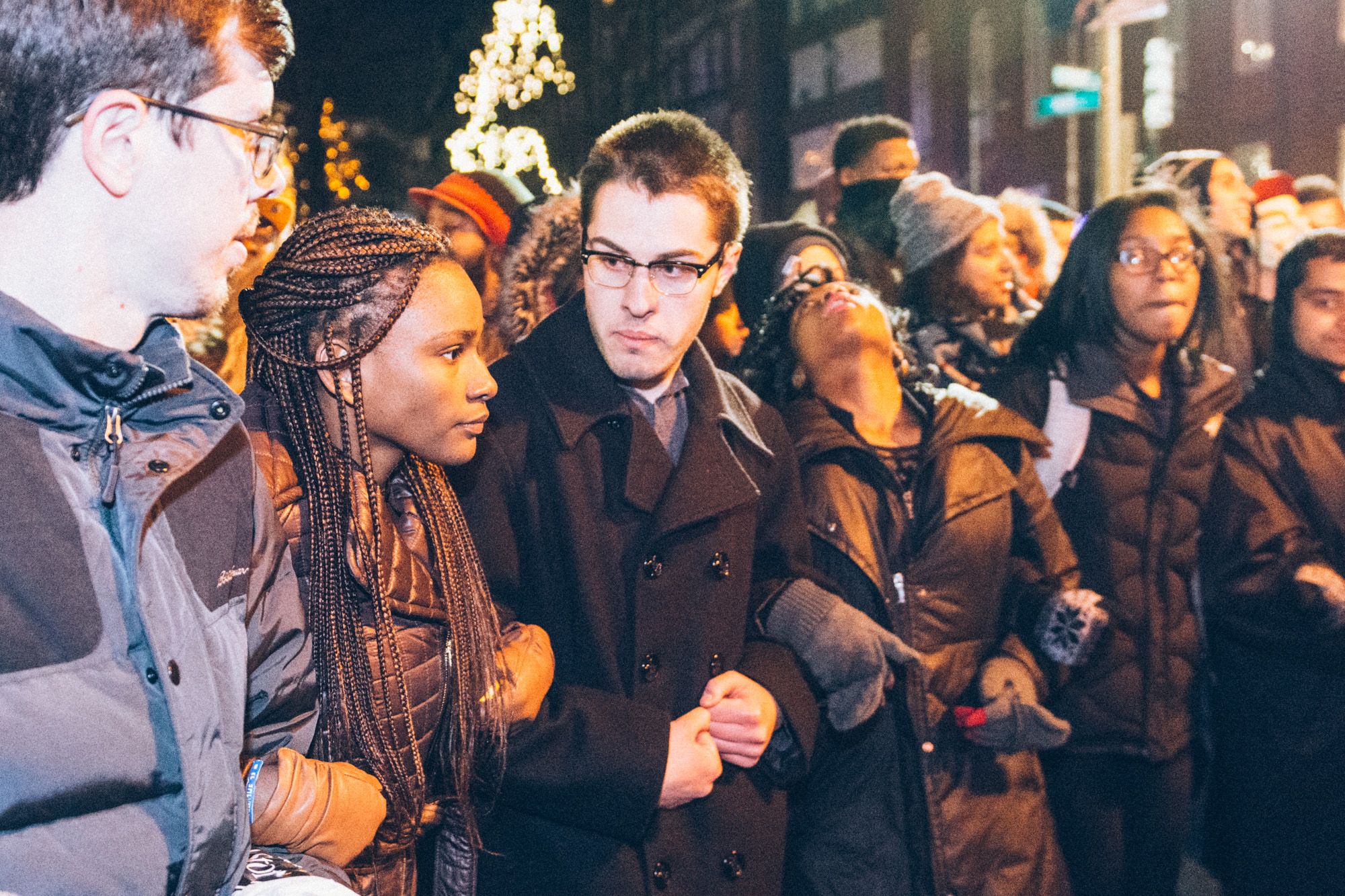 Protesters arm-in-arm listening to Rev. Sekou speak.