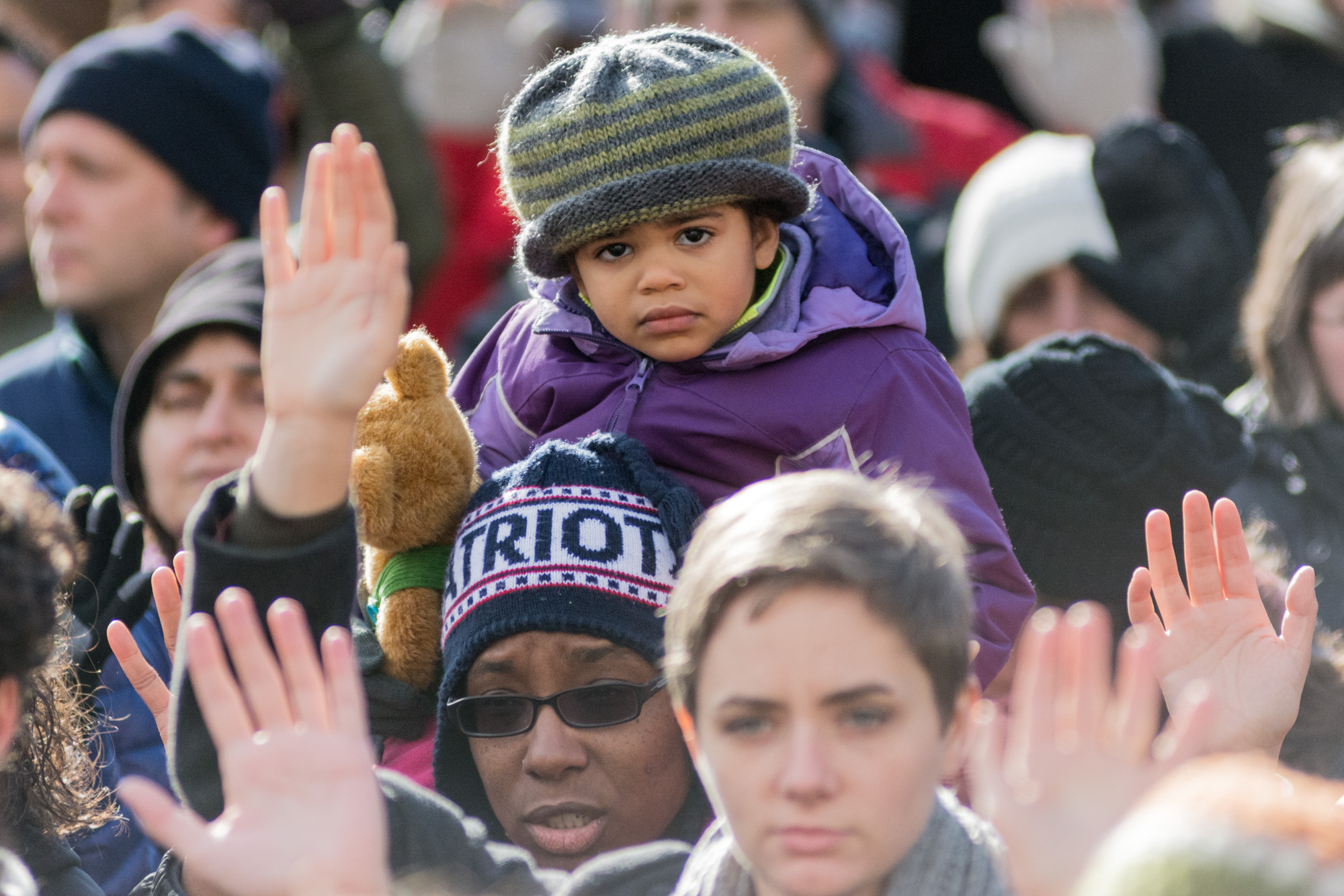 One of many children attending the protest on the shoulders of her father
