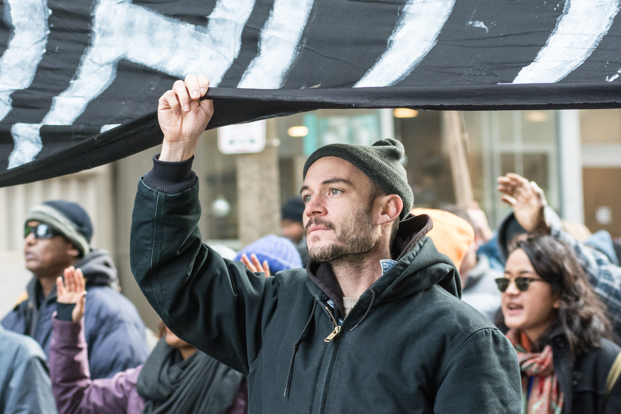 """A protester holding the middle of the """"Shut It Down"""" banner"""