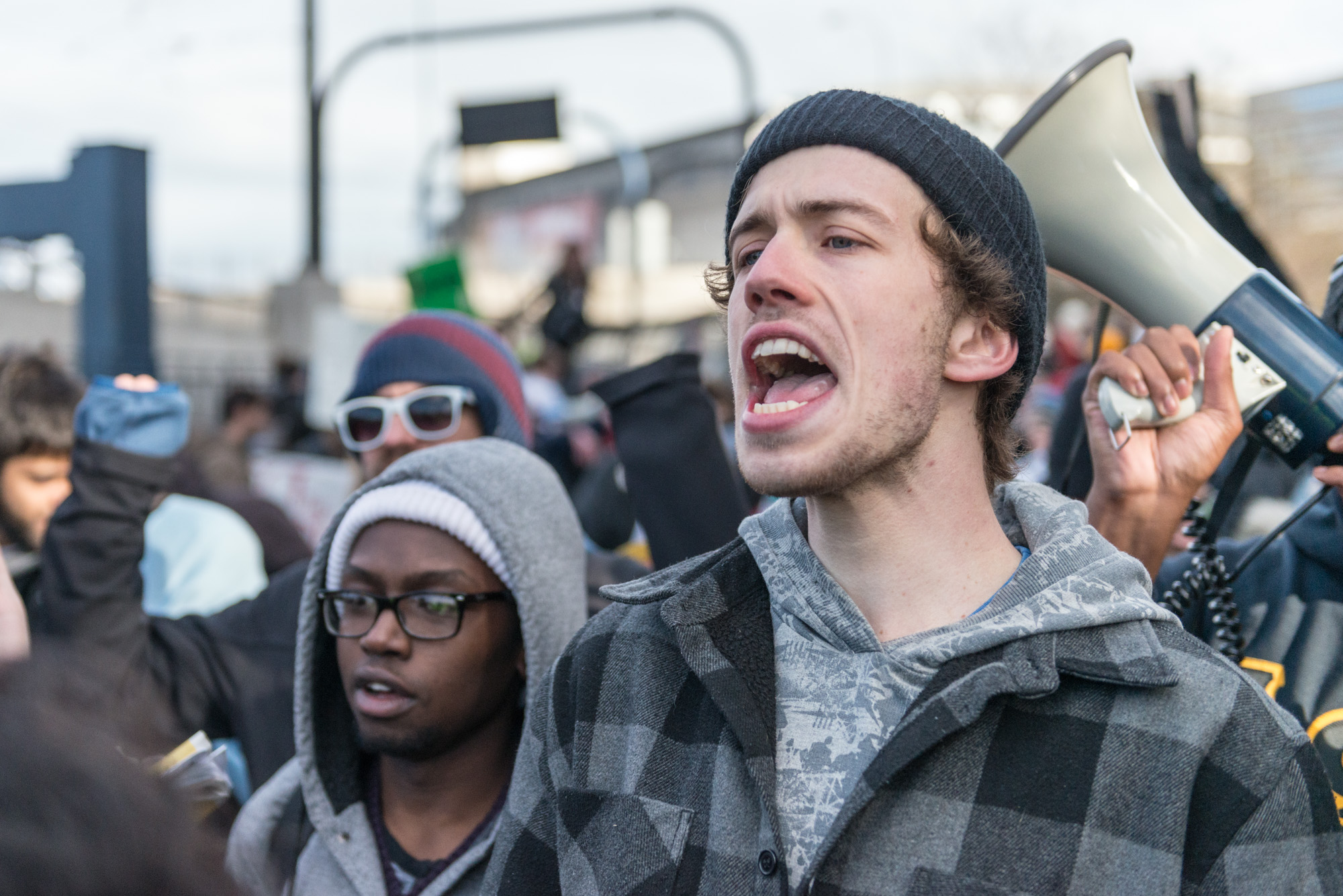 """Protester in front of the police fences yelling """"Who do you protect, who do you serve!"""""""