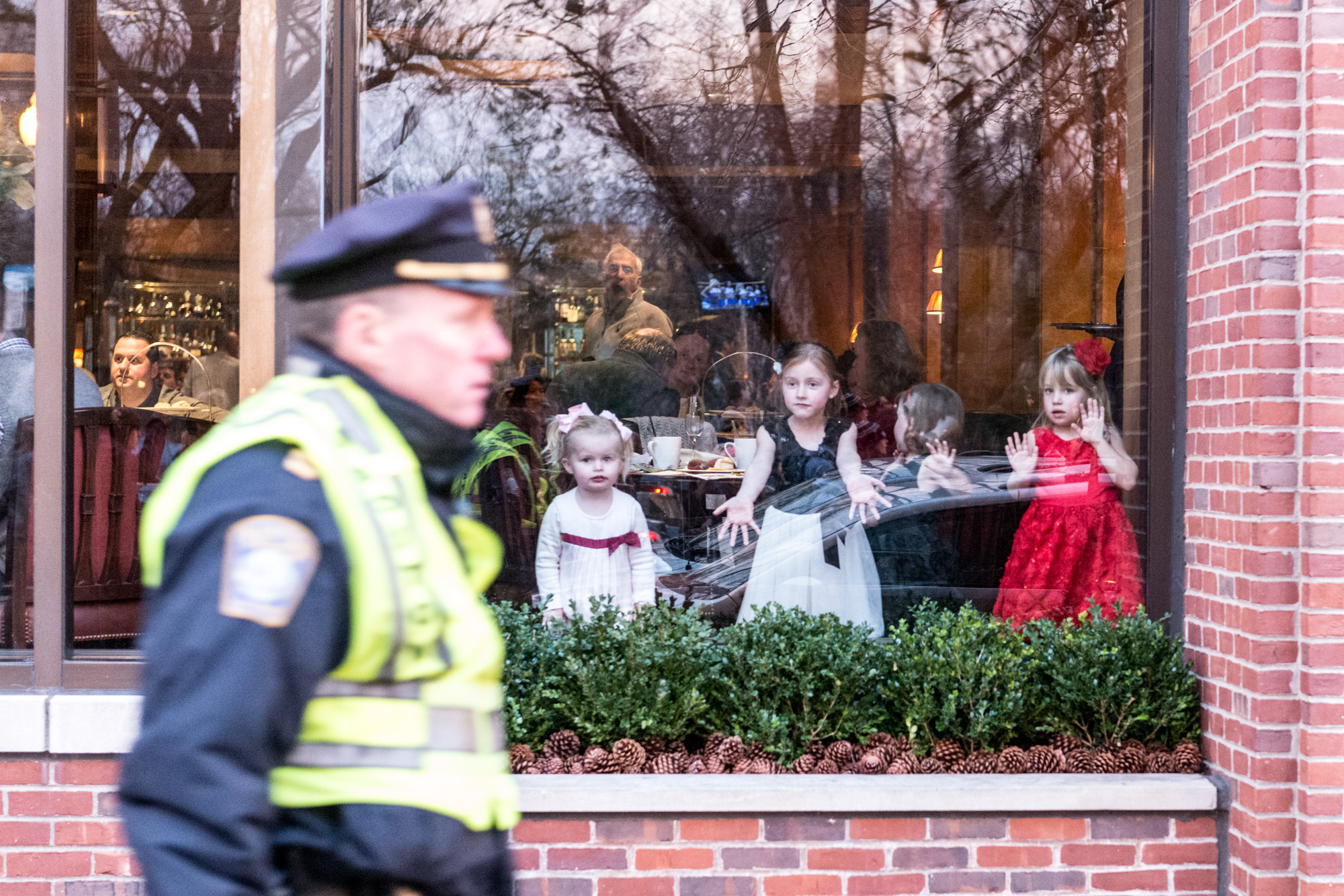 Three little girls looking at the marchers from a restaurant window on Boylston Street