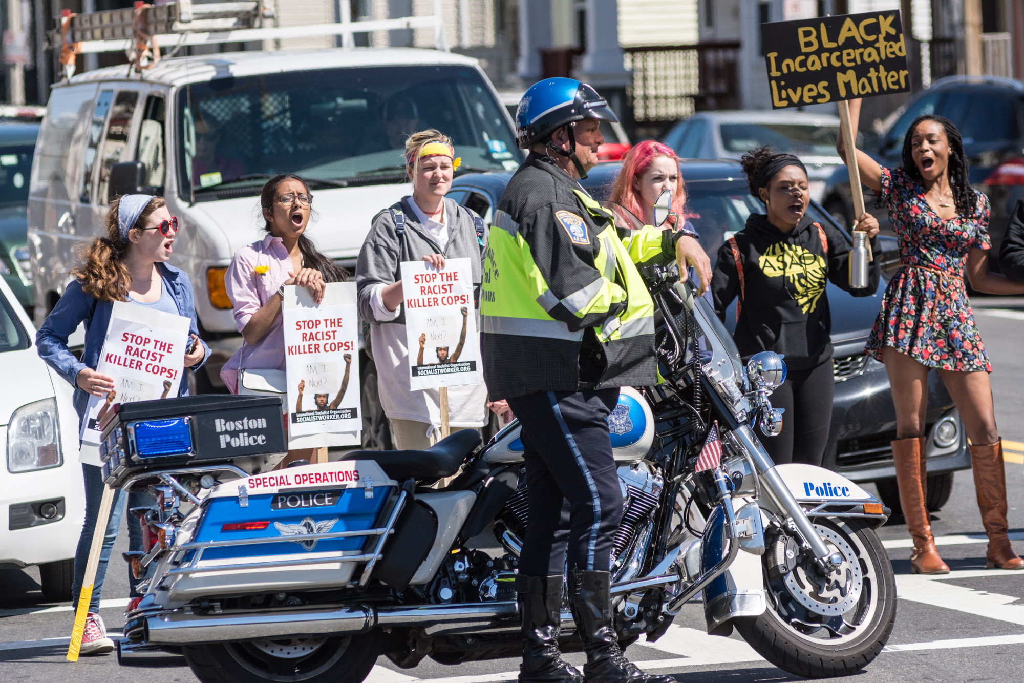 Motorcycle cop in the intersection while protesters block traffic