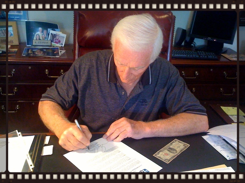 Captain Eugene A. Cernan signs the formal letter of flight certification, attesting the $2 bills history and 3x flight status. The signing took place in his study in Texas in August, 2010 -- after 44 years in his possession.