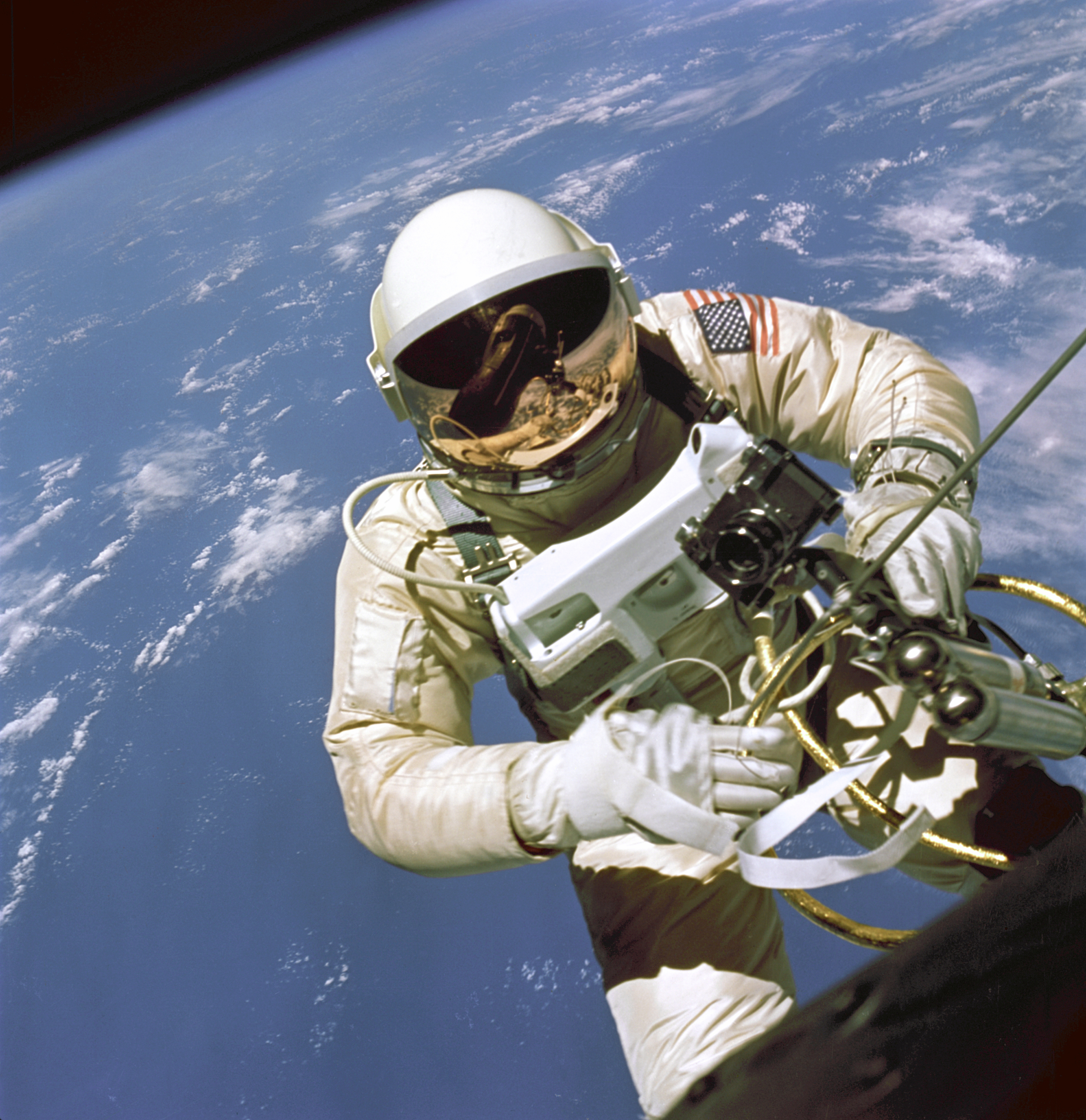 A famous image of astronaut Ed White's space walk on Gemini 4. If you look closely at the visor, you can see the reflection of the Gemini space capsule, the open hatch, and Jim McDivitt's image, snapping this picture through the capsule window.