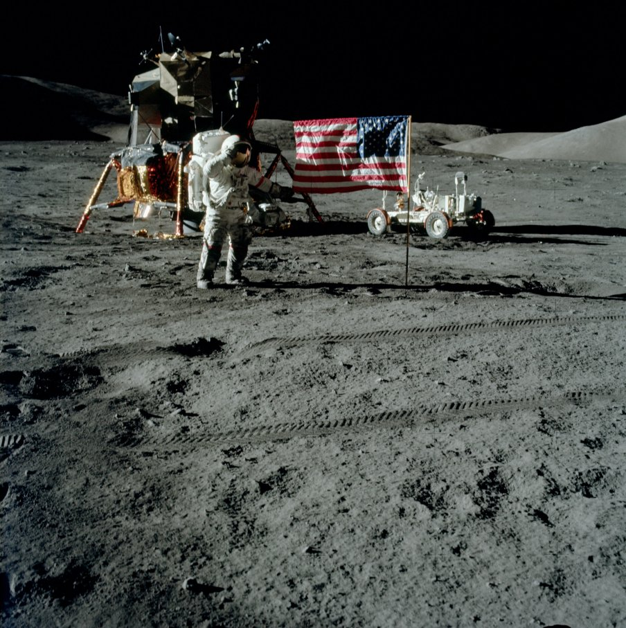 "Captain Cernan salutes the American flag while on the lunar surface in 1972 during the last Apollo landing mission. Behind him is the lunar module Challenger, which houses inside of it the flown $2 bill. Behind the flag is the Lunar Rover Vehicle, or ""moon buggy,"" the tracks of which can be seen directly in the foreground in the ancient lunar dust. Since there is no atmosphere on the moon, those track marks are still up on the moon, as they were, over 40+ years ago."