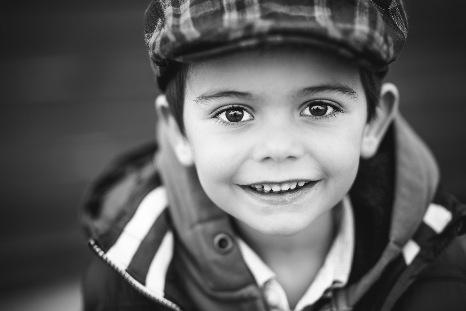 Black-and-white-photo-of-a-young-boy-in-a-cap-by-Stockholm-family-photographer.jpg