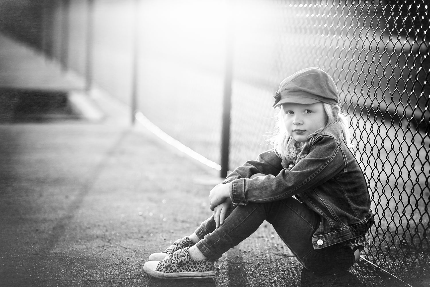 Black-and-white-portrait-of-a-girl-by-a-fence-by-familjefotografering-Sandra-Jolly.jpg