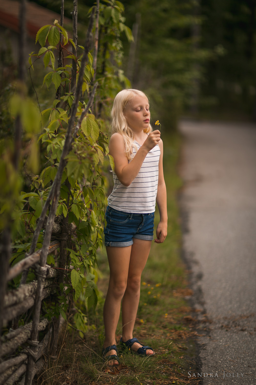 girl-smelling-flowers-in-sollentuna-by-familjefotograf-Sandra-Jolly.jpg