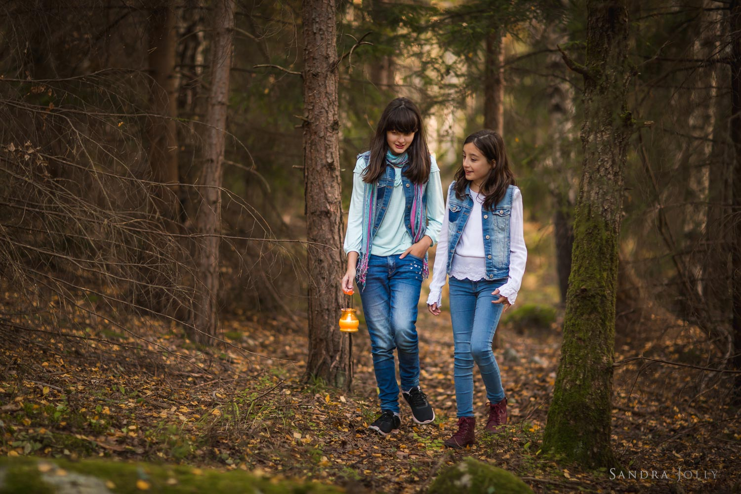 sisters-walking-in-woods-with-candle-by-Sandra-Jolly-familjefotografering.jpg