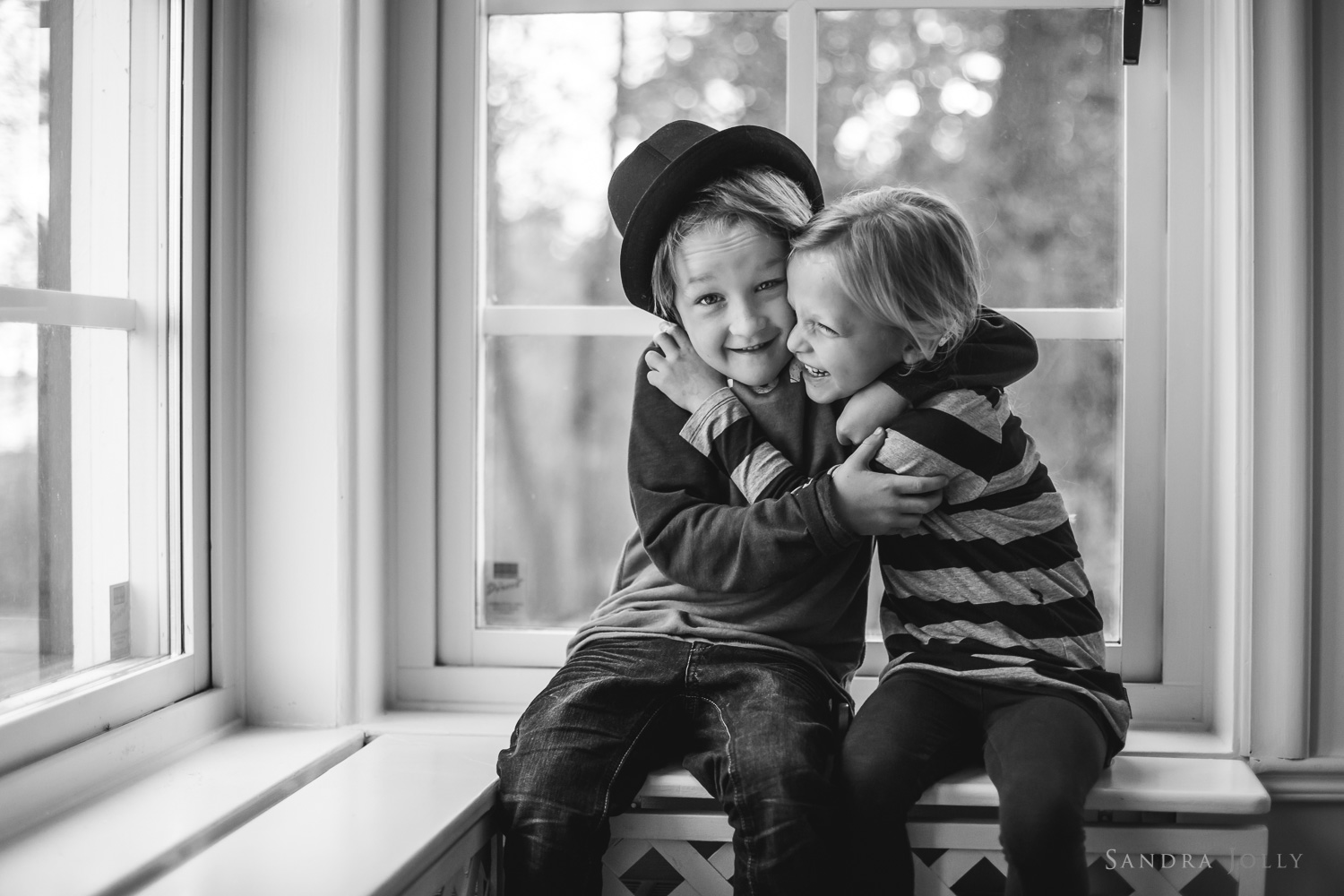 siblings-hugging-in-a-window-Täby-familjefotograf.jpg