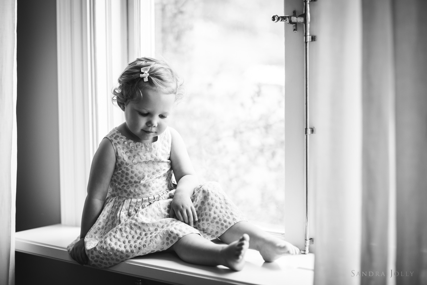 black-and-white-photo-of-girl-in-window-by-barnfotograf-stockholm-sandra-jolly.jpg