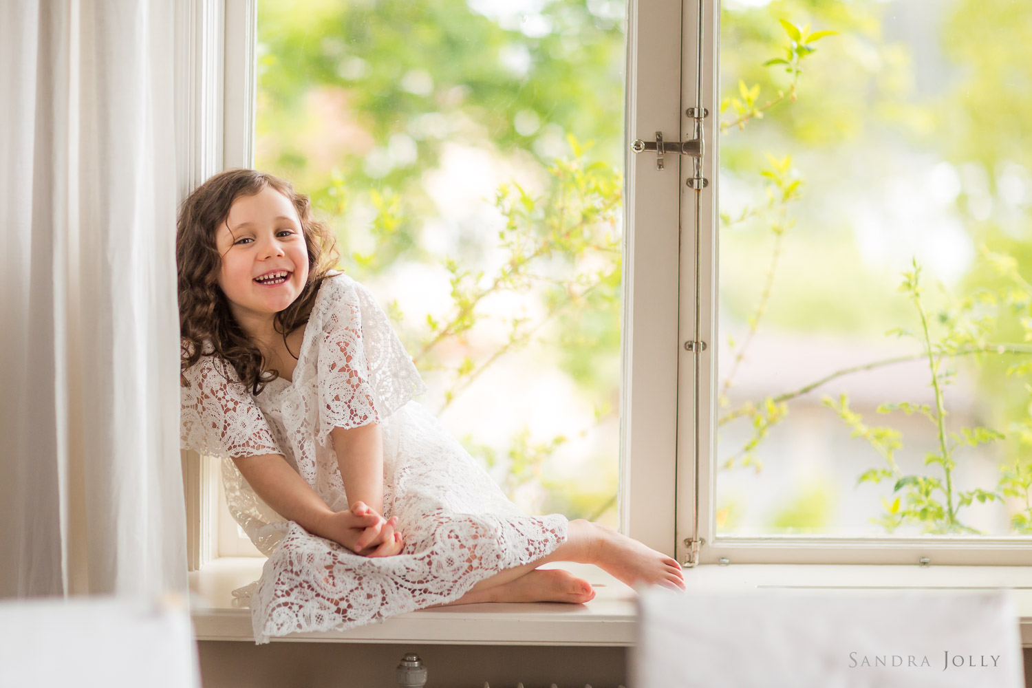 happy-girl-in-window-by-family-photographer-stockholm-sandra-jolly.jpg